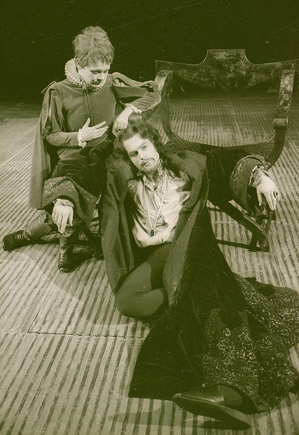 Viola sits behind Orsino, looking down at him while he stares into the distance in the 1969 production of Twelfth Night.