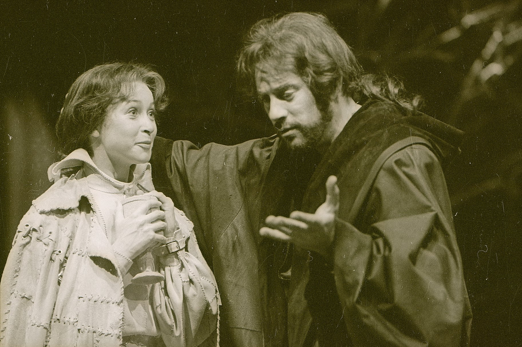 Viola, dressed as 'Ceasrio' in a travelling cloak and holding a goblet, talks to Orsino who is dressed in a dark robe in the 1979 production of Twelfth Night.