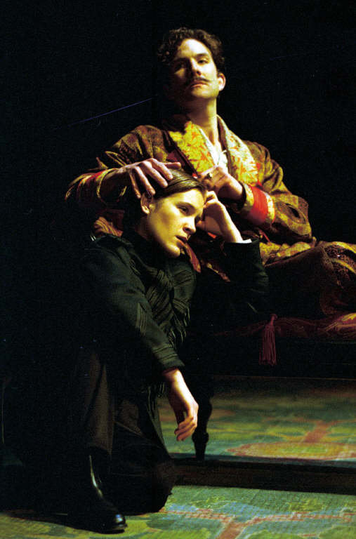 Viola, dressed as 'Cesario' and all in black, sits at the foot of Orsion's chair, with her head in his lap. Orsino, in a brightly coloured dressing gown, strokes her hair in the 2001 production of Twelfth Night.