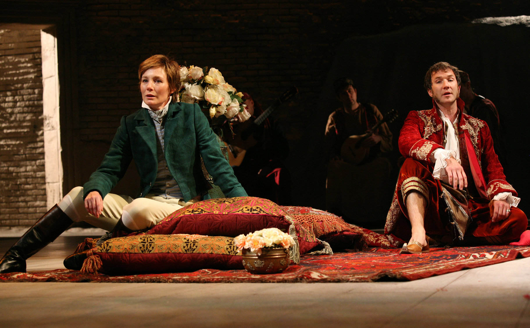 Viola dressed as 'Ceasrio' sits on scatter cushions on the floor, facing away from Orsino. Orsino, dressed in an elaborate red and gold robe with lace cuffs, sits on the floor behind her some distance away  in the 2009 production of Twelfth Night.