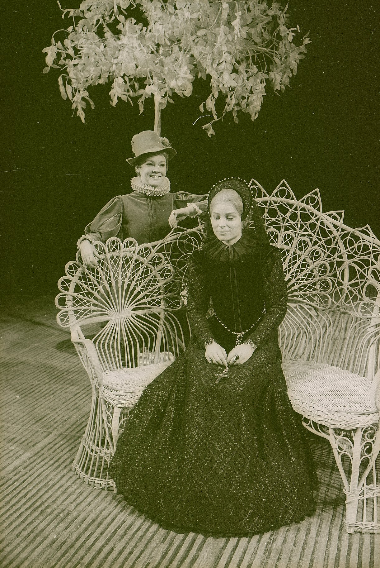 Olivia sittiing on an elaborate bench. Cesario (played by Judi Dench) stands benind the bench