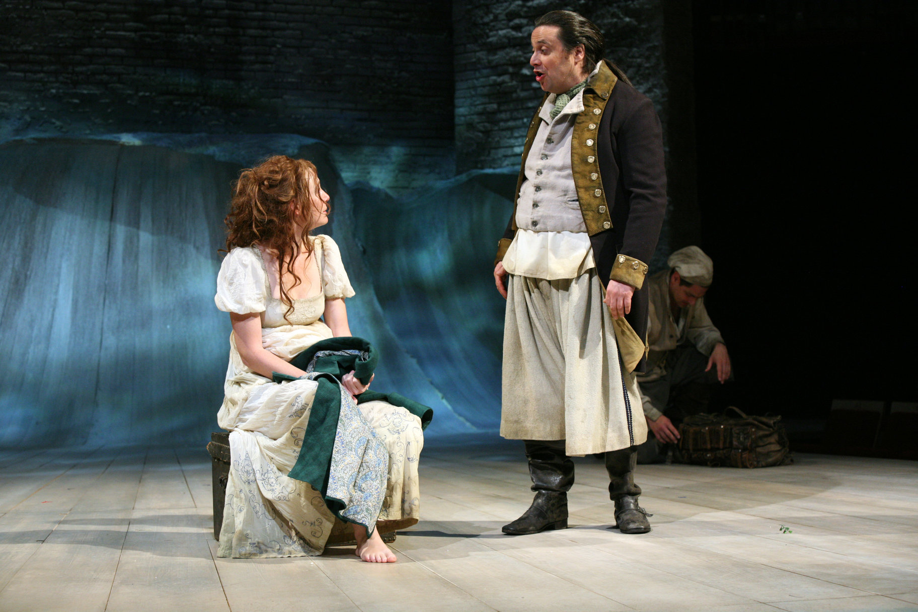 Viola sits on a luggage trunk holding Sebastian's coat, in a white dress, talking to the captain who stands next to her in disheveled uniform on the shore of Illyria in the 2007 production of Twelfth Night.