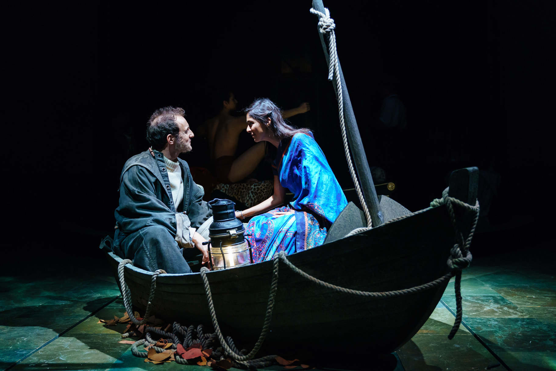 Viola wearing a blue sari and the captain wearing an old coat sit in a small rowing boat on the shore of Illyria with a lantern between them in the 2017 production of Twelfth Night.