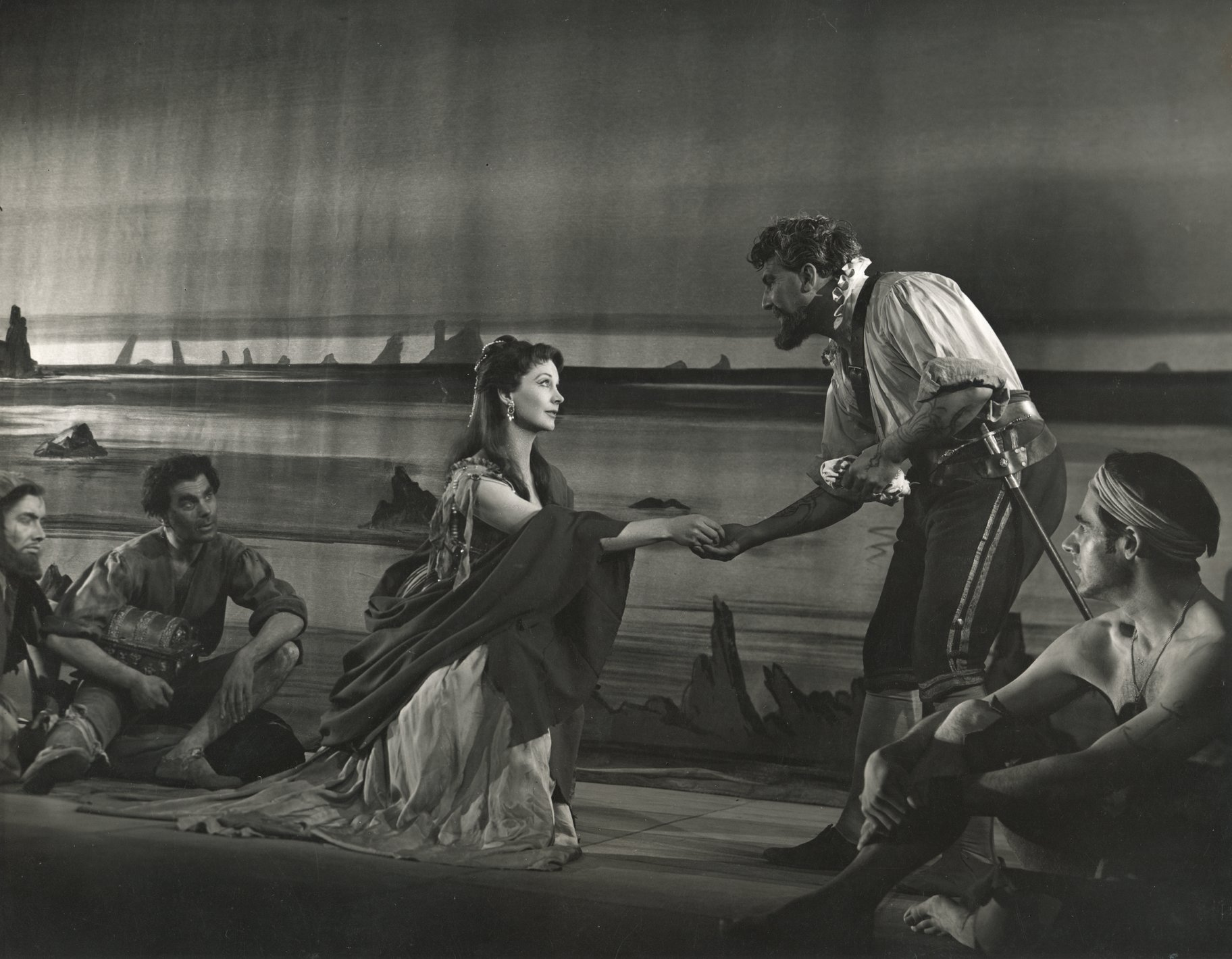 Viola reaches out to the captain while kneeling in a sleeveless dress and shawl on the shore of Illyria in the 1955 production of Twelfth Night.