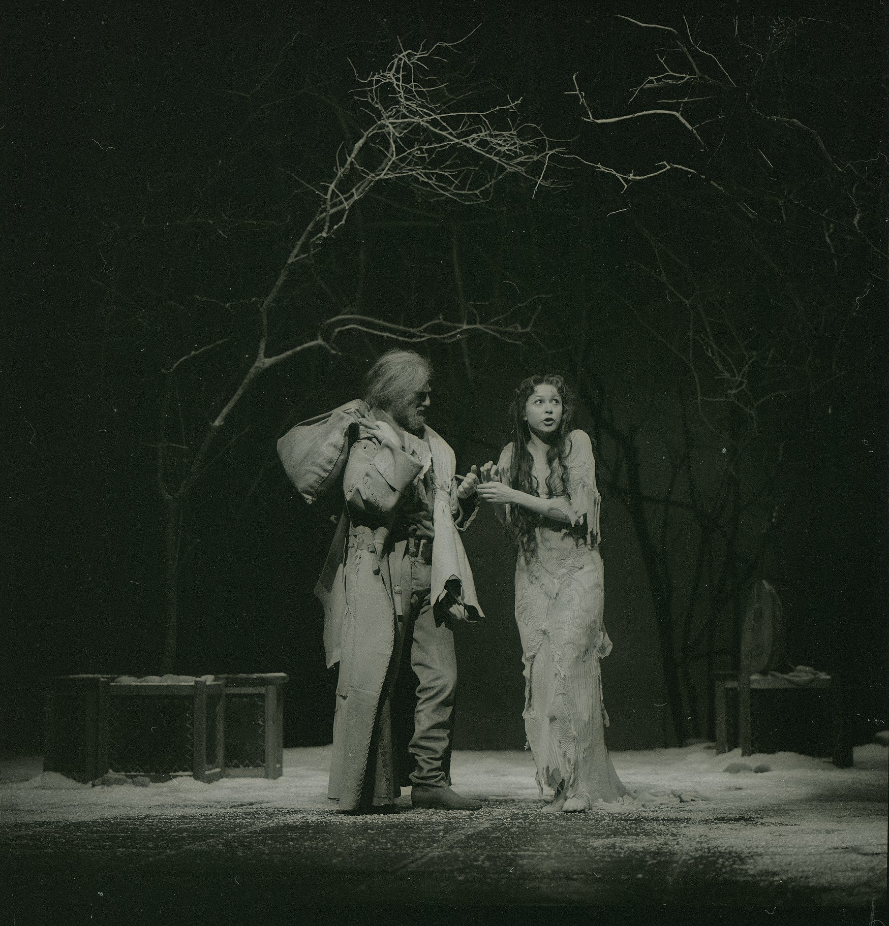 Viola, dressed in a ragged and torn white dress, stands with the captain who has a bag of possessions over his shoulder. There is scattered sand across the shore of Illyria in the 1983 production of Twelfth Night.