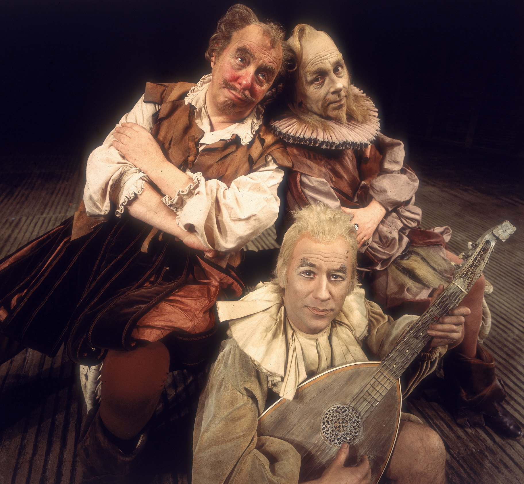 Sir Toby (left), Feste (center) and Sir Andrew (right) seated together.
