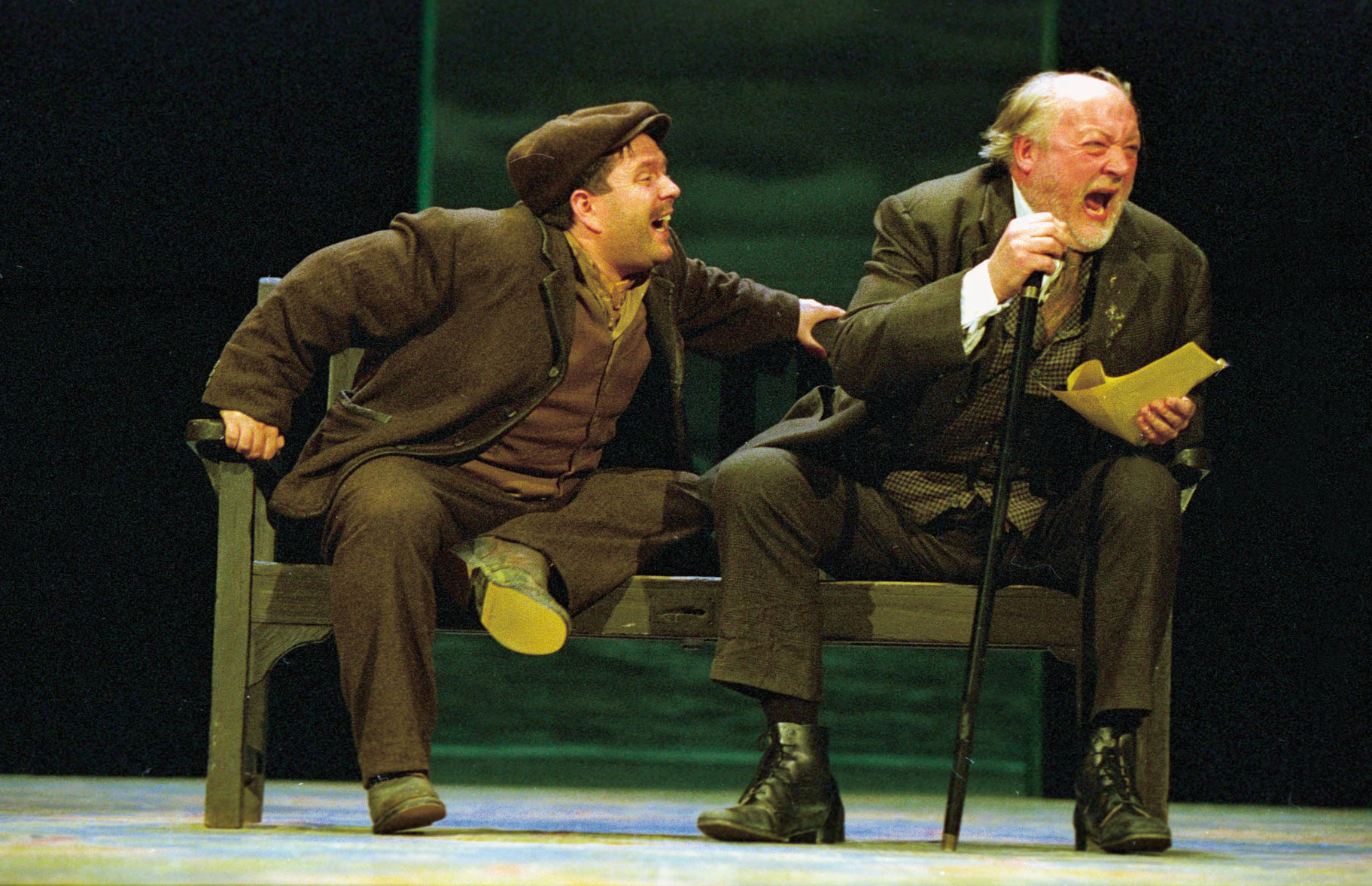 Fabian (left) and Sir Toby (right) sitting on a bench, laughing at the contents of a letter