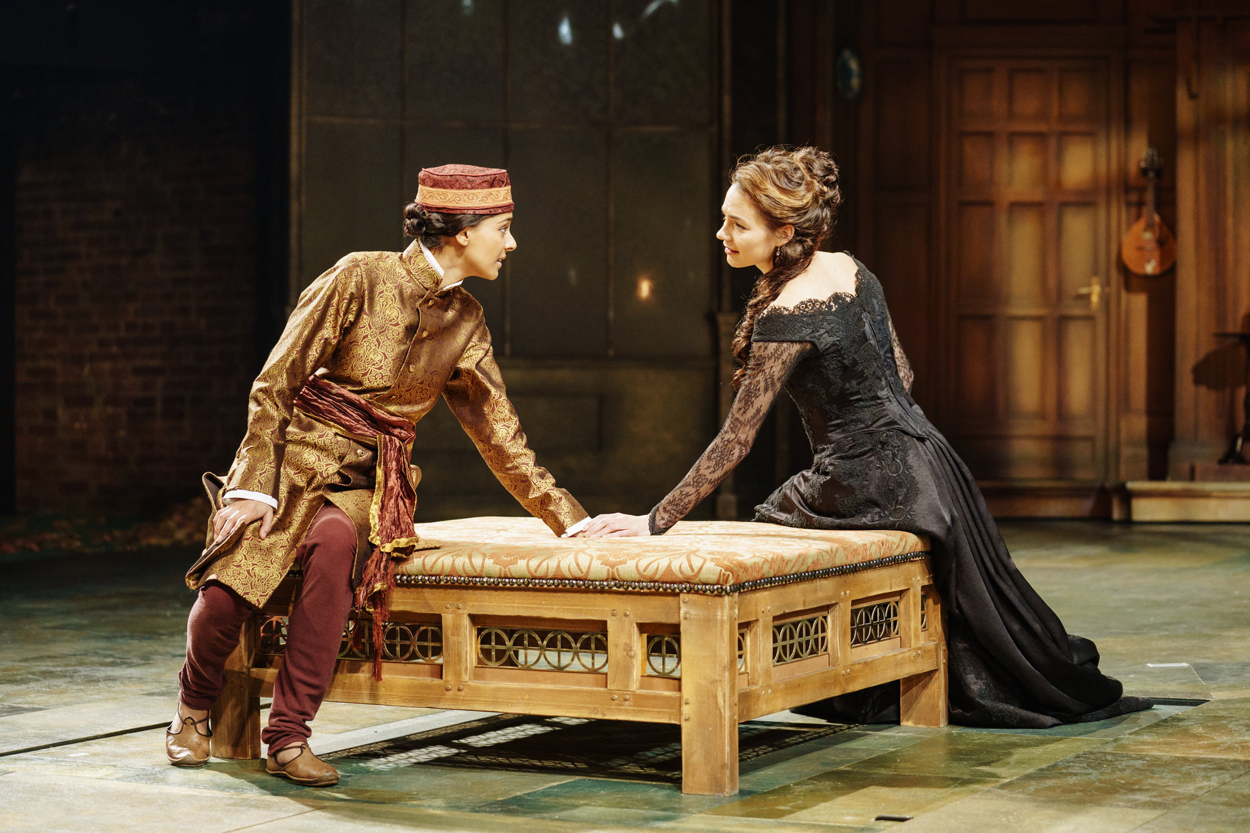 Olivia touches 'Cesario's' hand as they both sit on a square bench in the 2017 production of Twelfth Night.