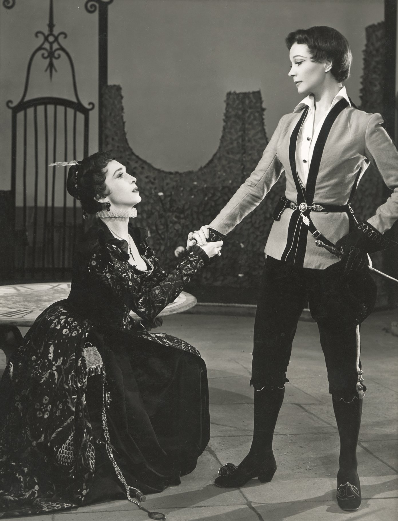 Olivia kneels in front of 'Cesario' and clutches 'his' hand in the 1955 production of Twelfth Night.