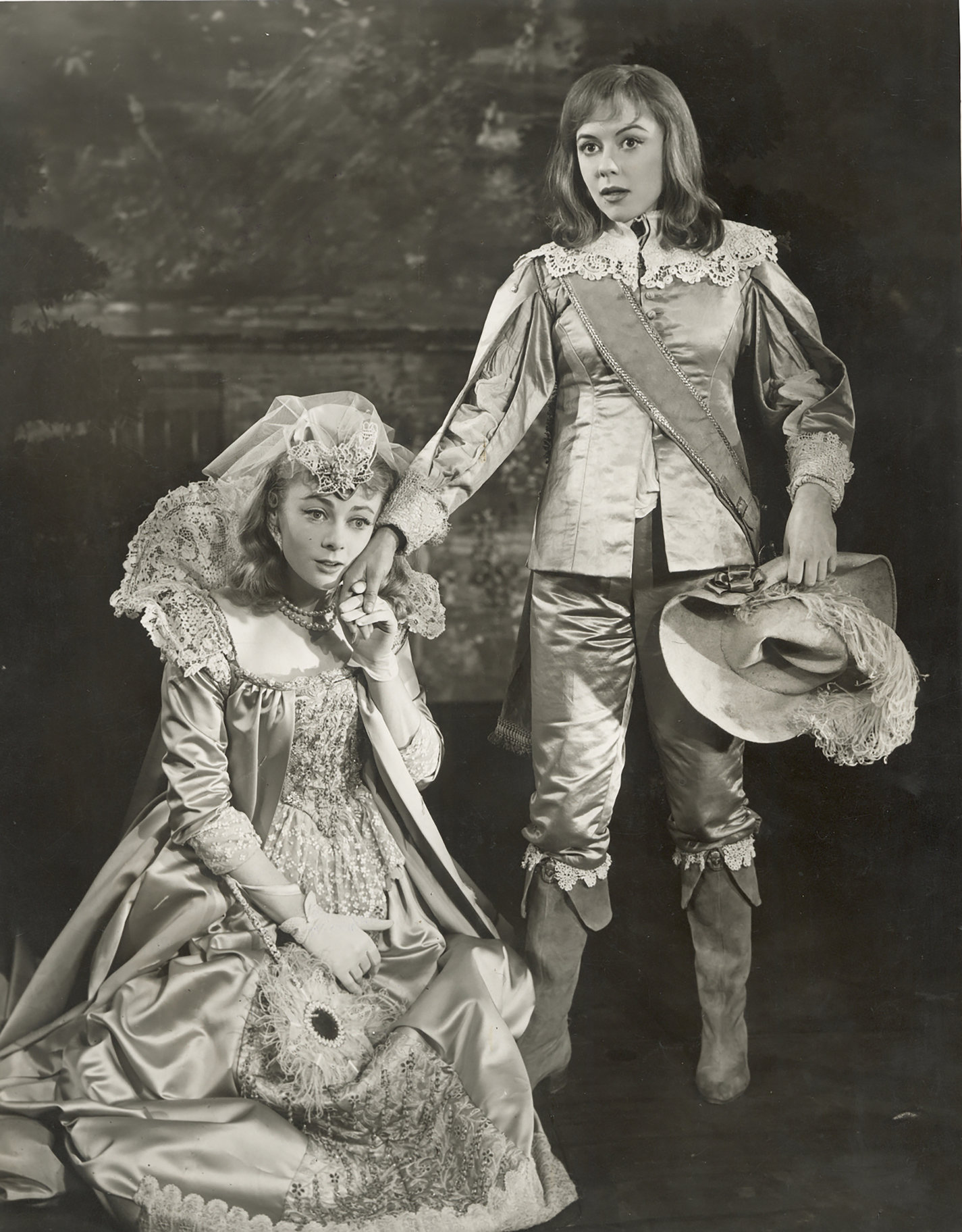Olivia kneels, touching 'Ceasrio's' hand to her face in the 1958 production of Twelfth Night.
