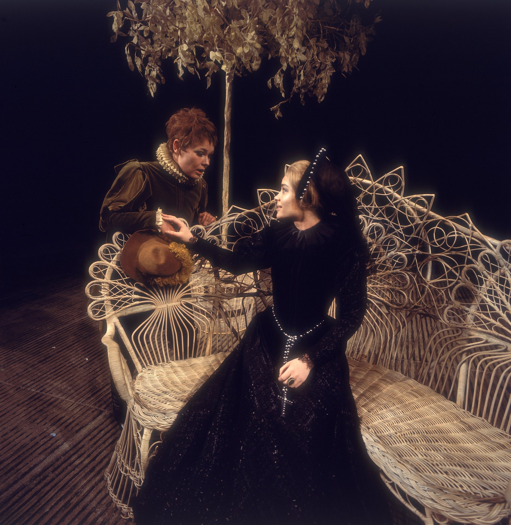 Olivia reaches out to 'Cesario', touching 'his' hand over the back of a garden bench in the 1969 production of Twelfth Night.