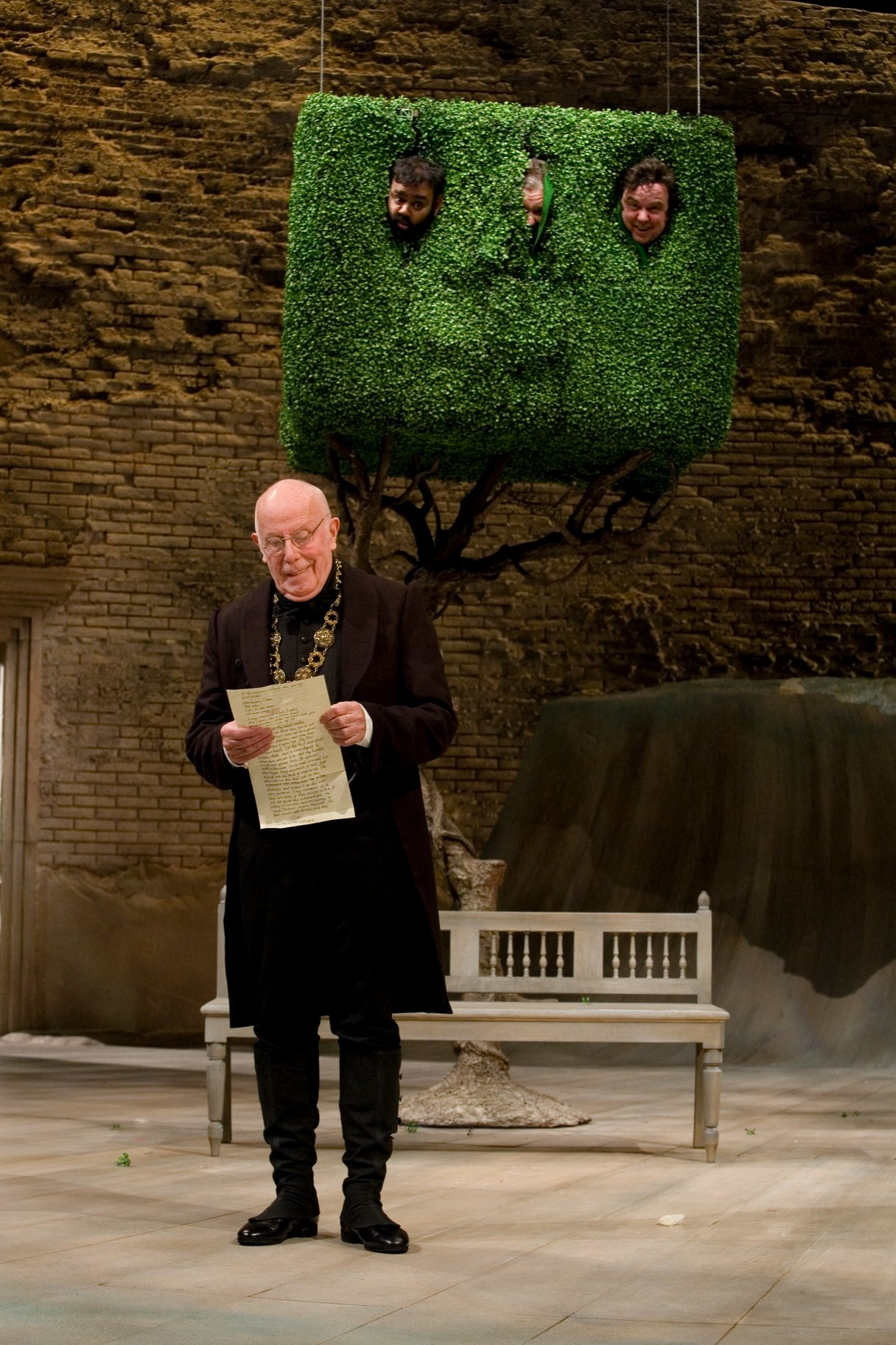Malvolio dressed in black with a gold chain reads a letter while watched by Sir Toby, Sir Andrew and Fabain who are hidden in a tree above him, with their faces sticking out in the 2009 production of Twelfth Night.