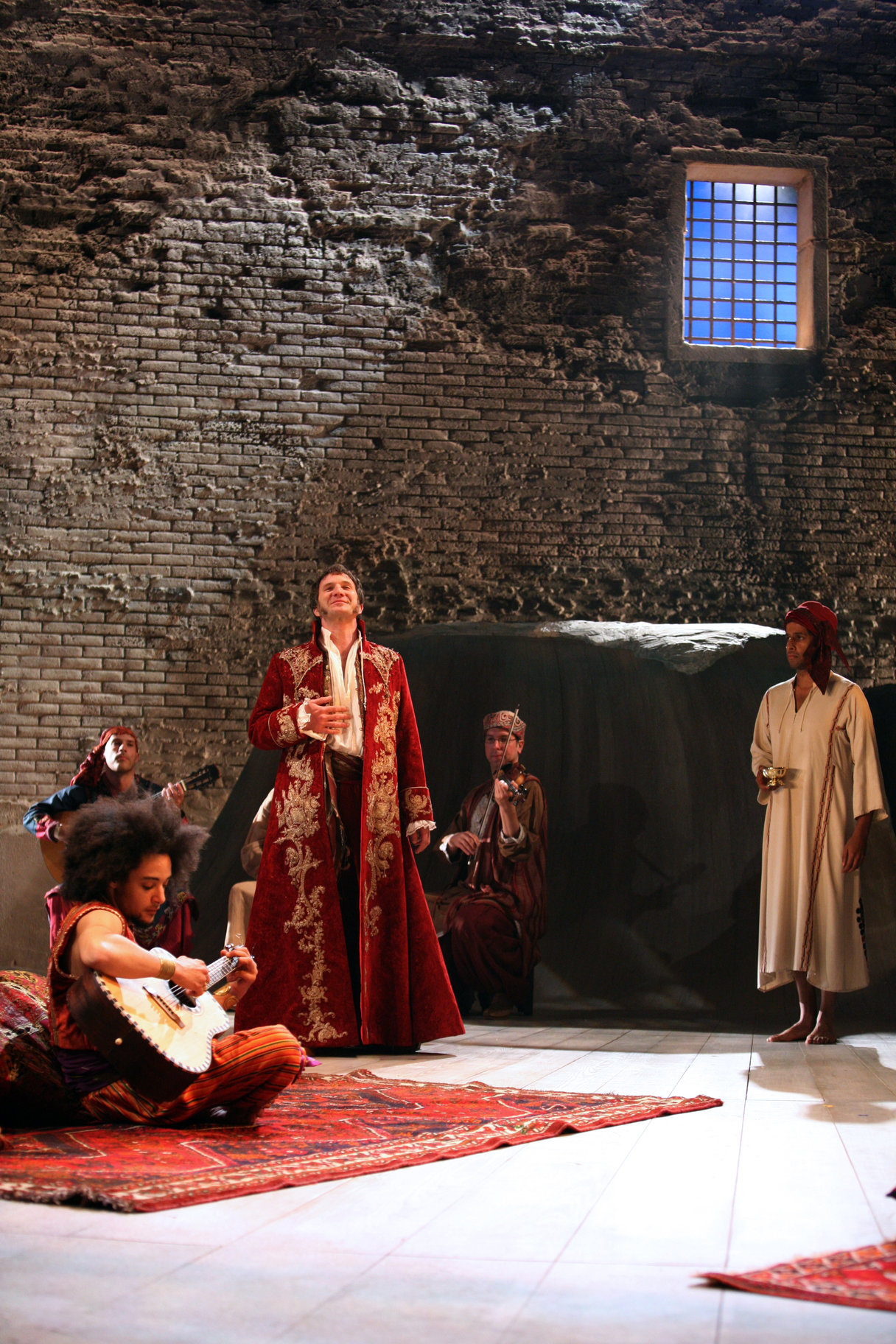 Orsino stands surrounded by musicians who are sat on the floor on rugs, he is wearing a red and gold robe, in the 2009 production of Twelfth Night.