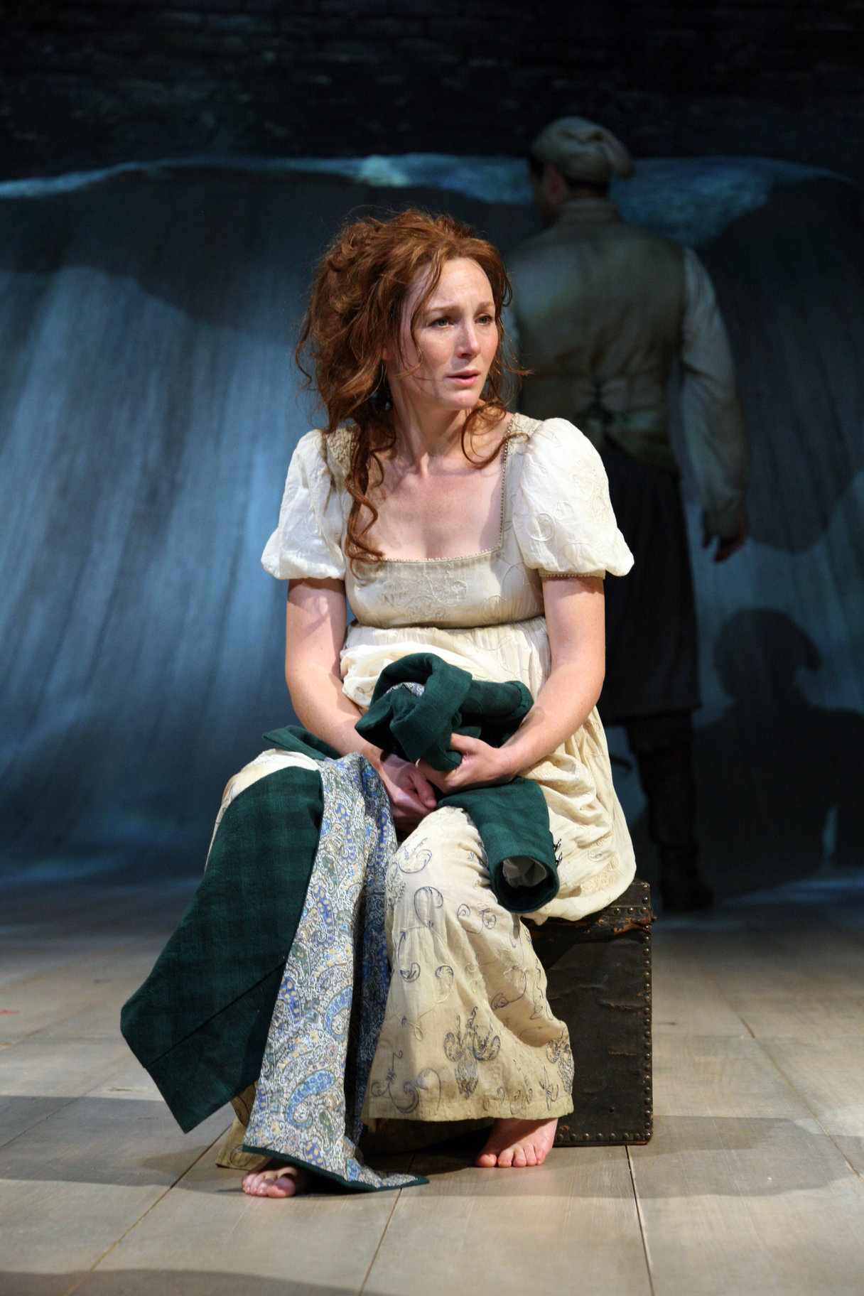 Viola, dressed in a tattered white dress and holding her brother's green coat, sits on the shore after being in the shipwreck, in the 2009 production of Twelfth Night.