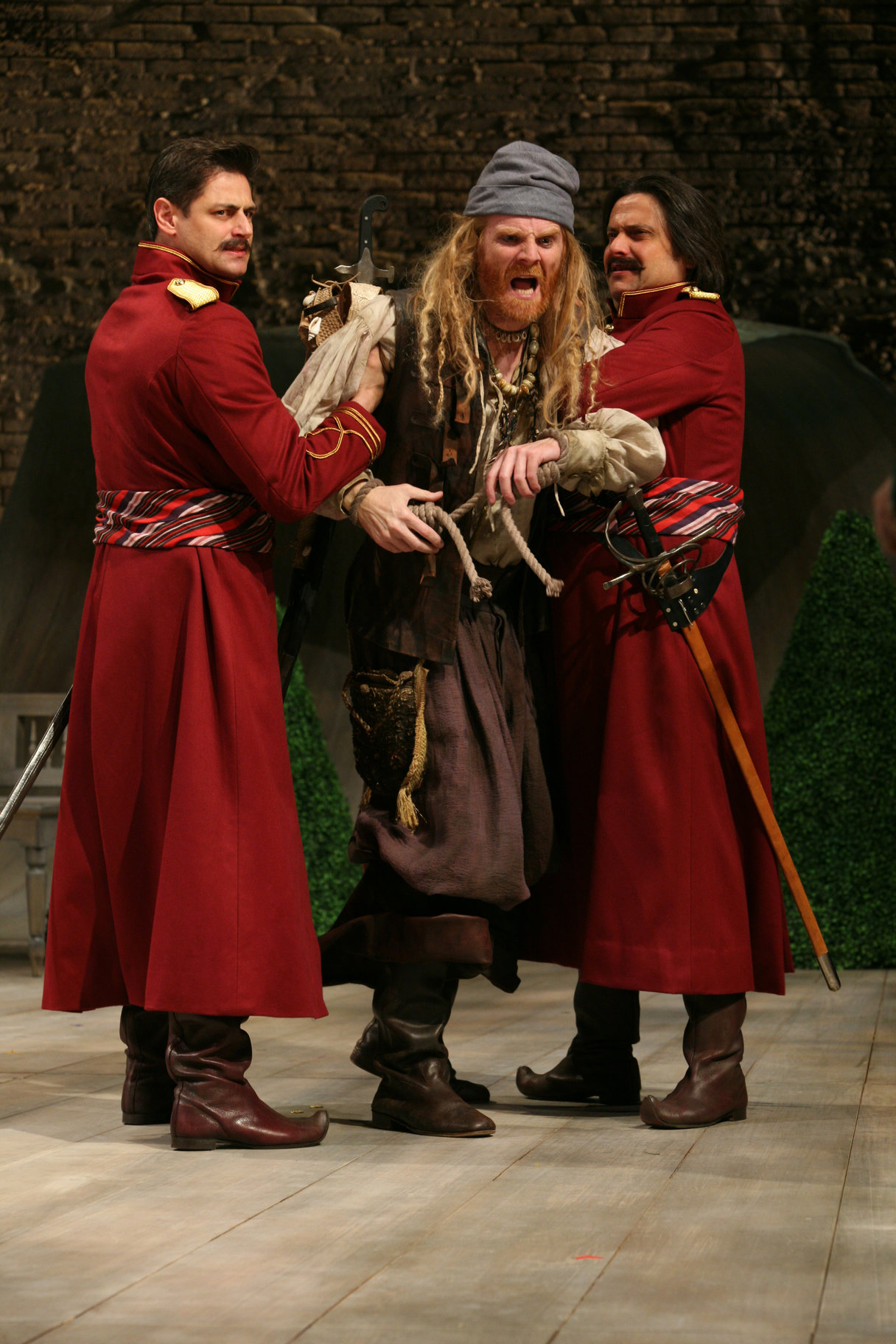 Antonio is arrested by two guards wearing red as he fights to pull away, shouting, in the 2009 production of Twelfth Night.