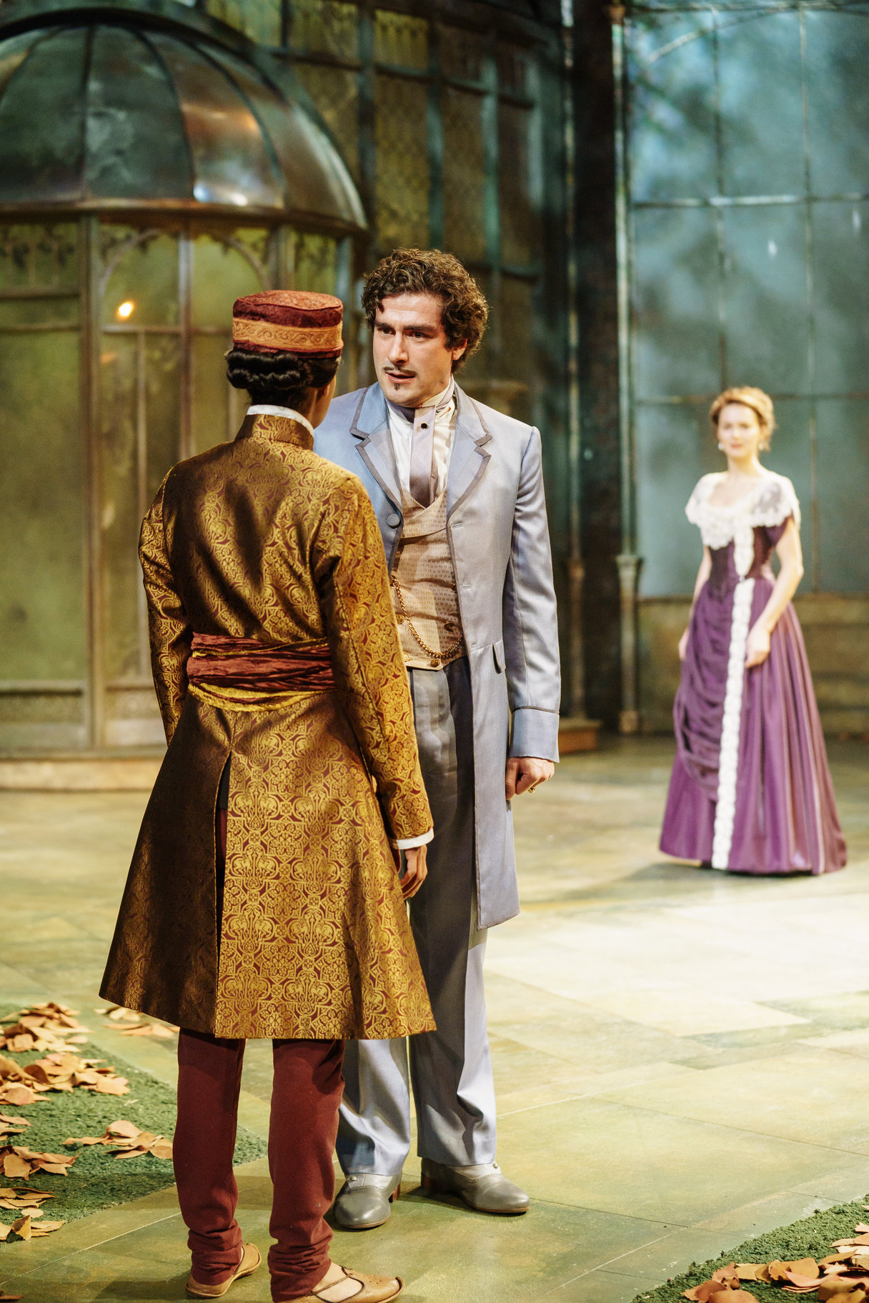 ​Orsino talks to Cesario outside Olivia's house while Olivia, dressed in a purple dress, watches in the 2017 production of Twelfth Night.