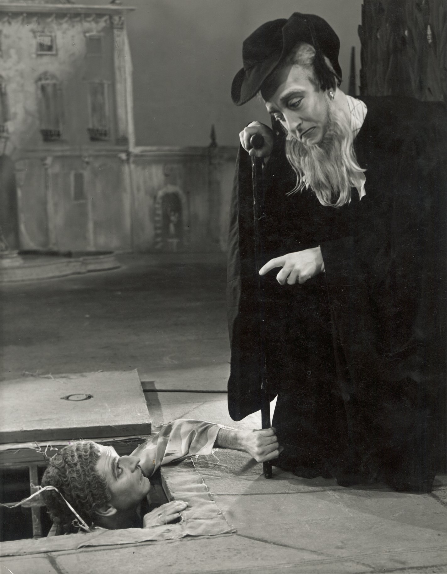 Feste dressed as a priest talks down to Malvolio who reaches out from a hole in the ground in the 1955 production of Twelfth Night.
