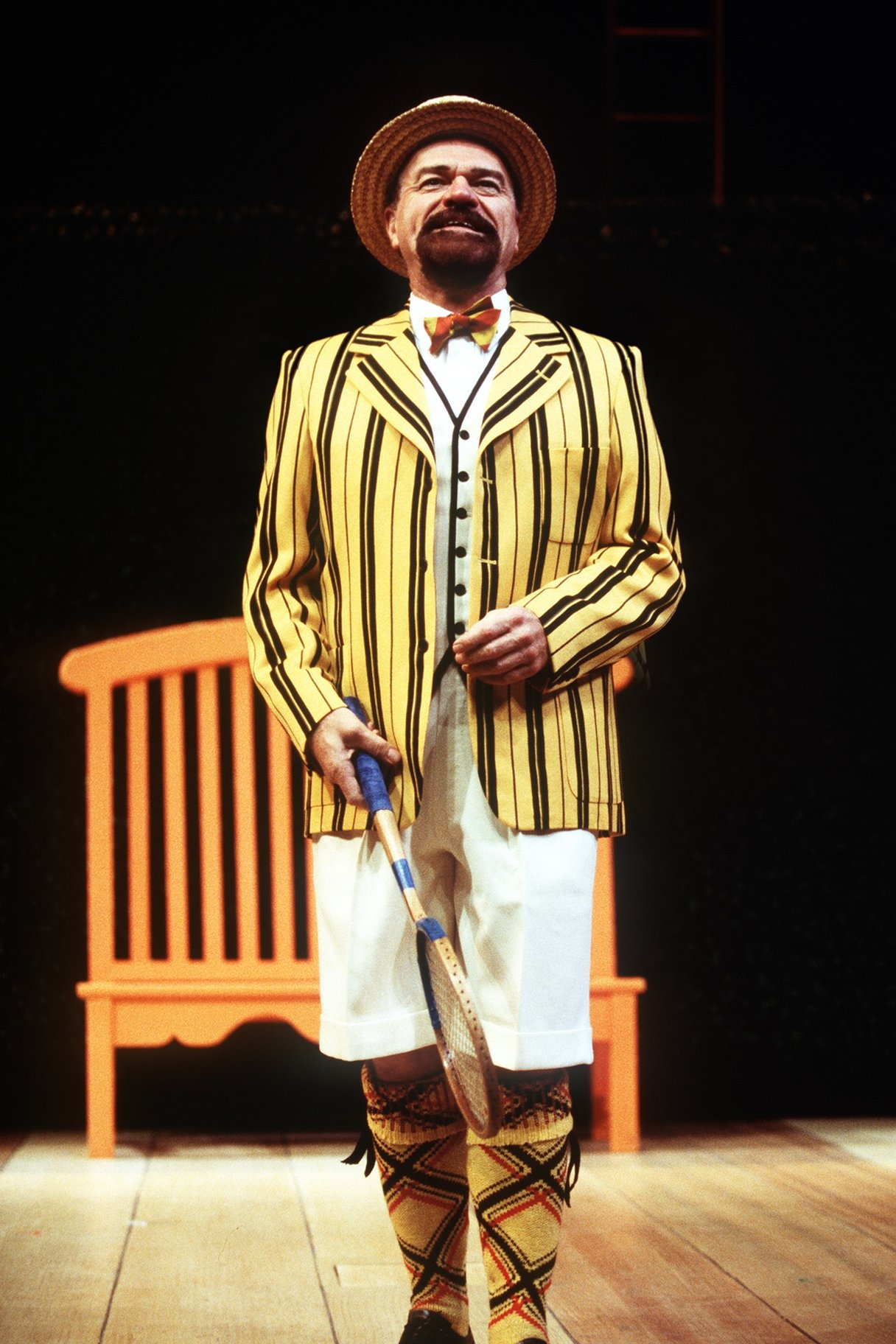 Malvolio stands wearing a bright yellow striped blazer and patterned stockings, holding a wooden tennis racket and grinning in the 1998 production of Twelfth Night.