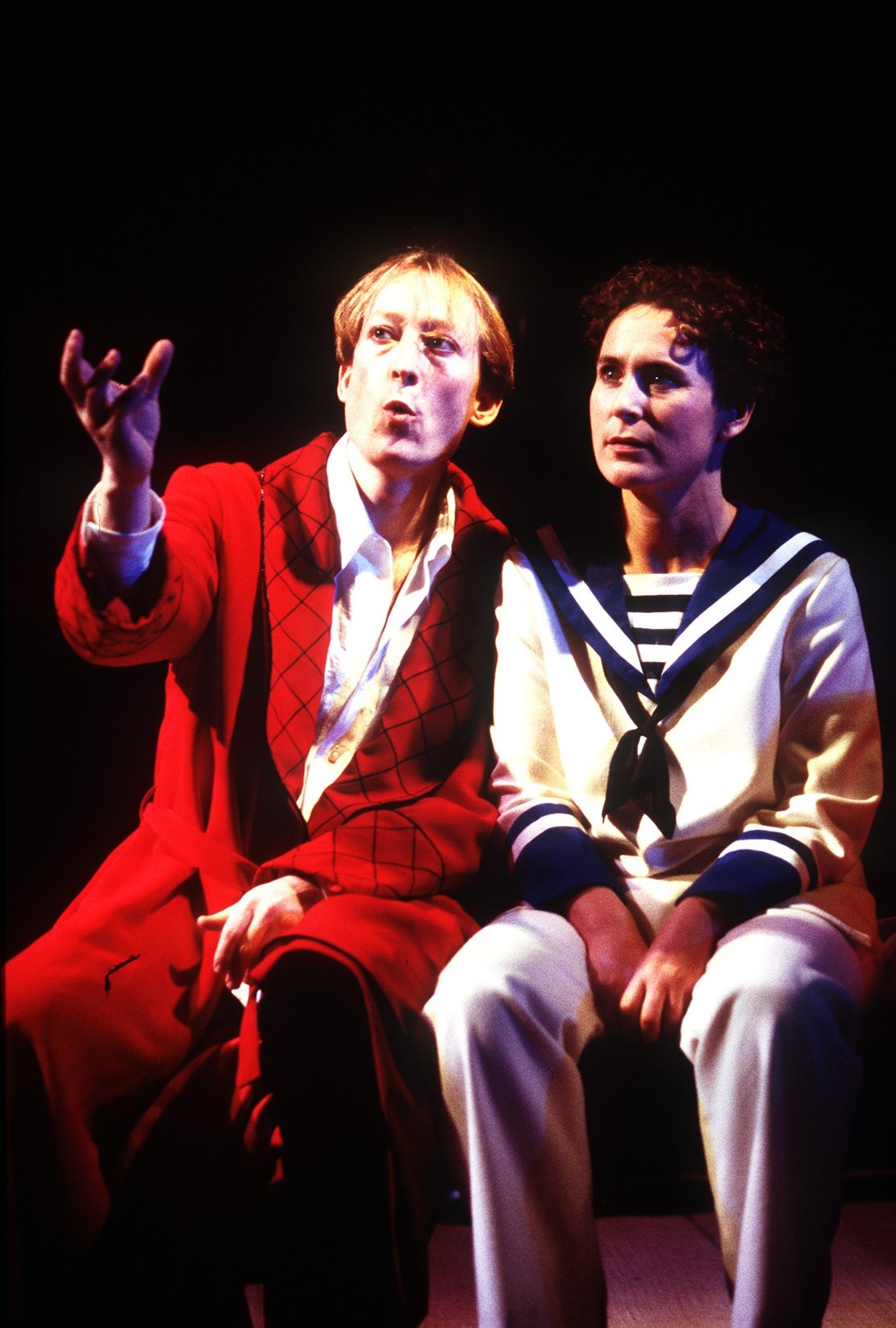Orsino and Viola sit side by side with Orsino in a red dressing gown and Viola dressed as Cesario in a sailor's uniform in the 1998 production of Twelfth Night.