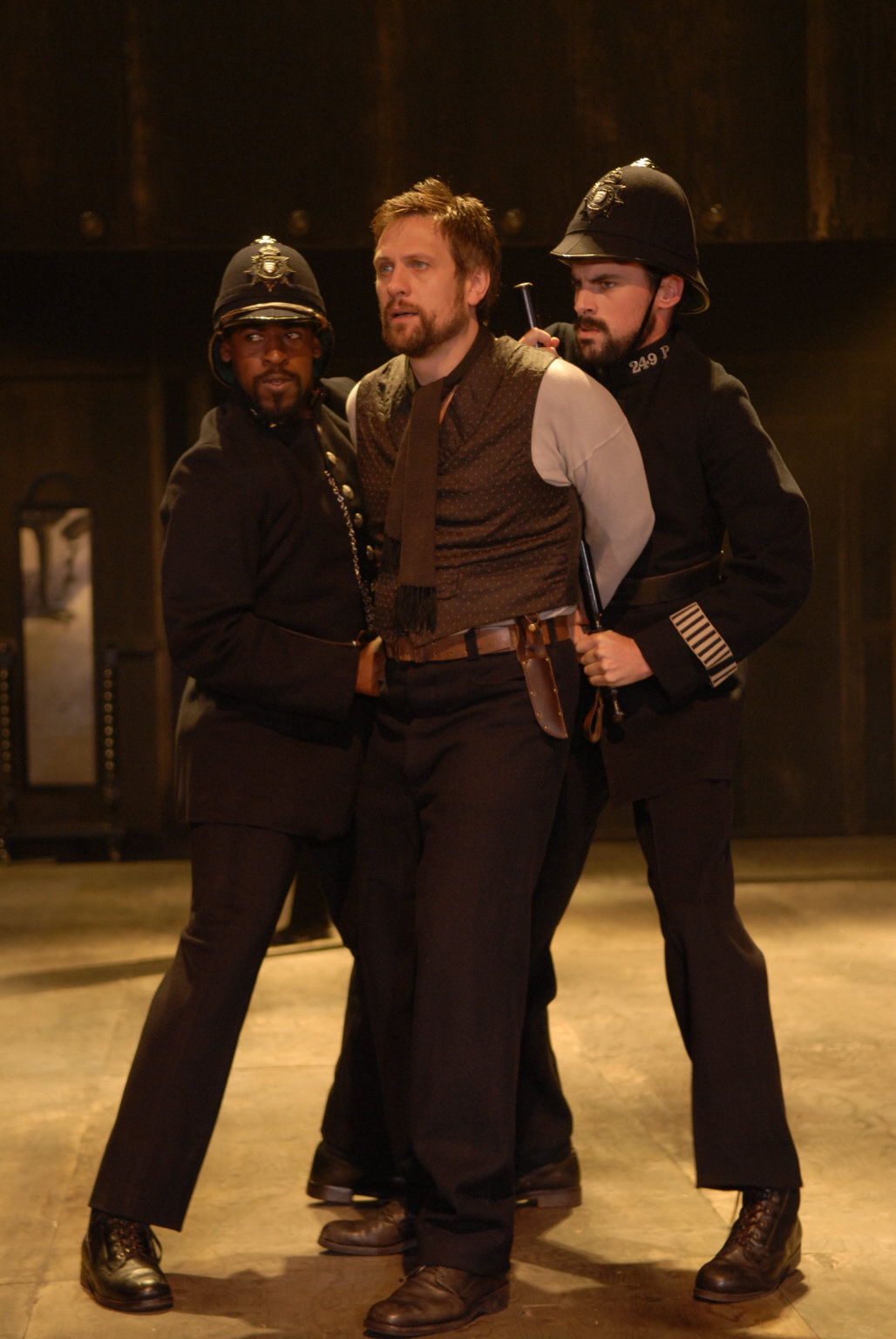 Antonio is arrested by two men dressed as policemen in uniform as he stands and looks surprised in the 2009 production of Twelfth Night.