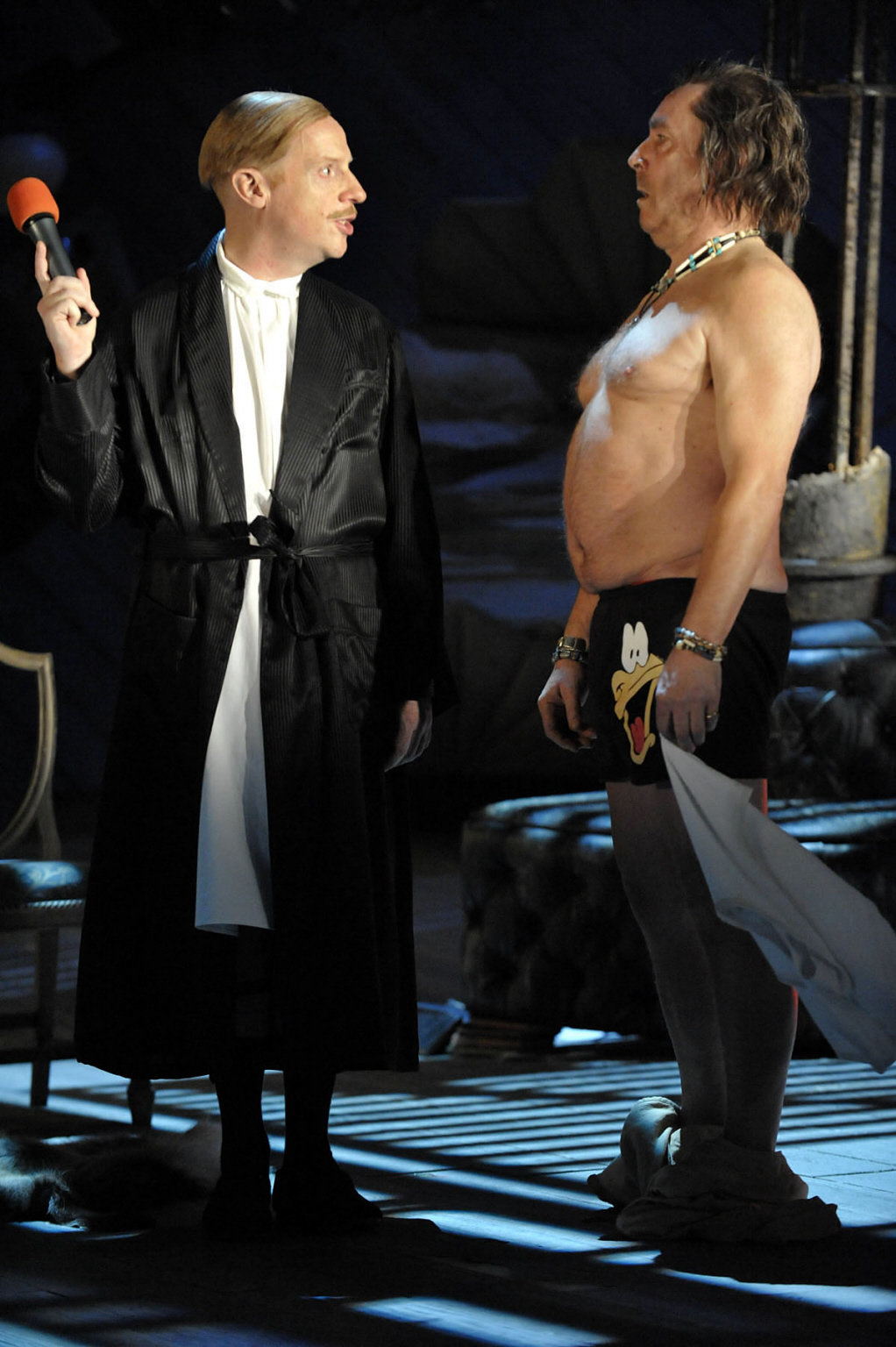 Malvolio is dressed in a nightgown and holding a red microphone out of Sir Toby's reach as he stands and looks at him, topless and in Disney boxer shorts in the 2012 production of Twelfth Night.