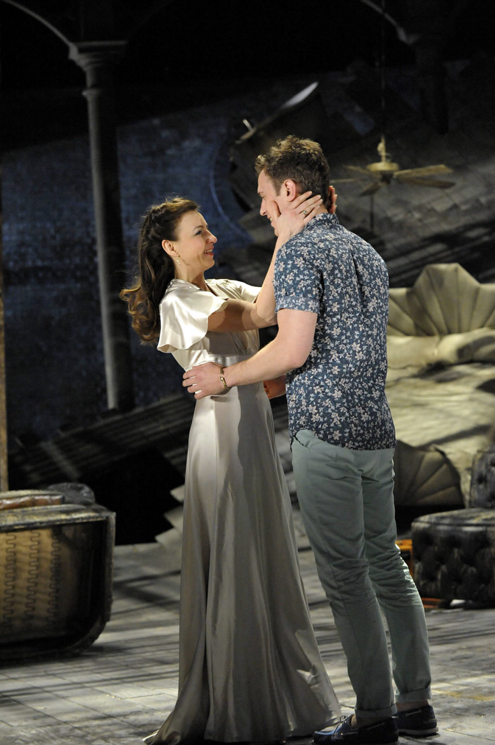 Sebastian dressed in a blue shirt and Olivia in a white silk dress look at each other in the 2012 production of Twelfth Night.