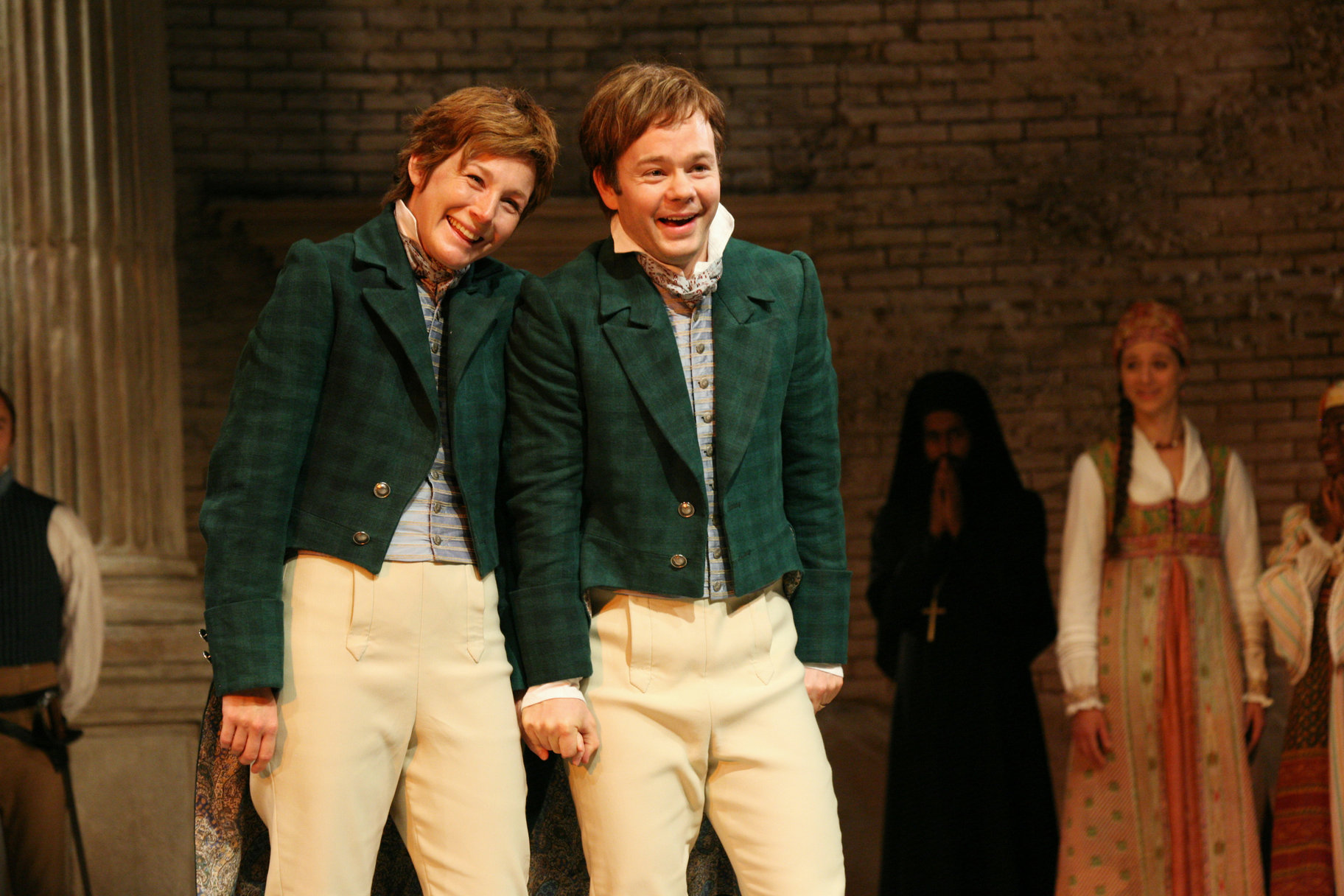 Viola and Sebastian laugh side by side in green jackets and beige trousers in the 2009 production of Twelfth Night.