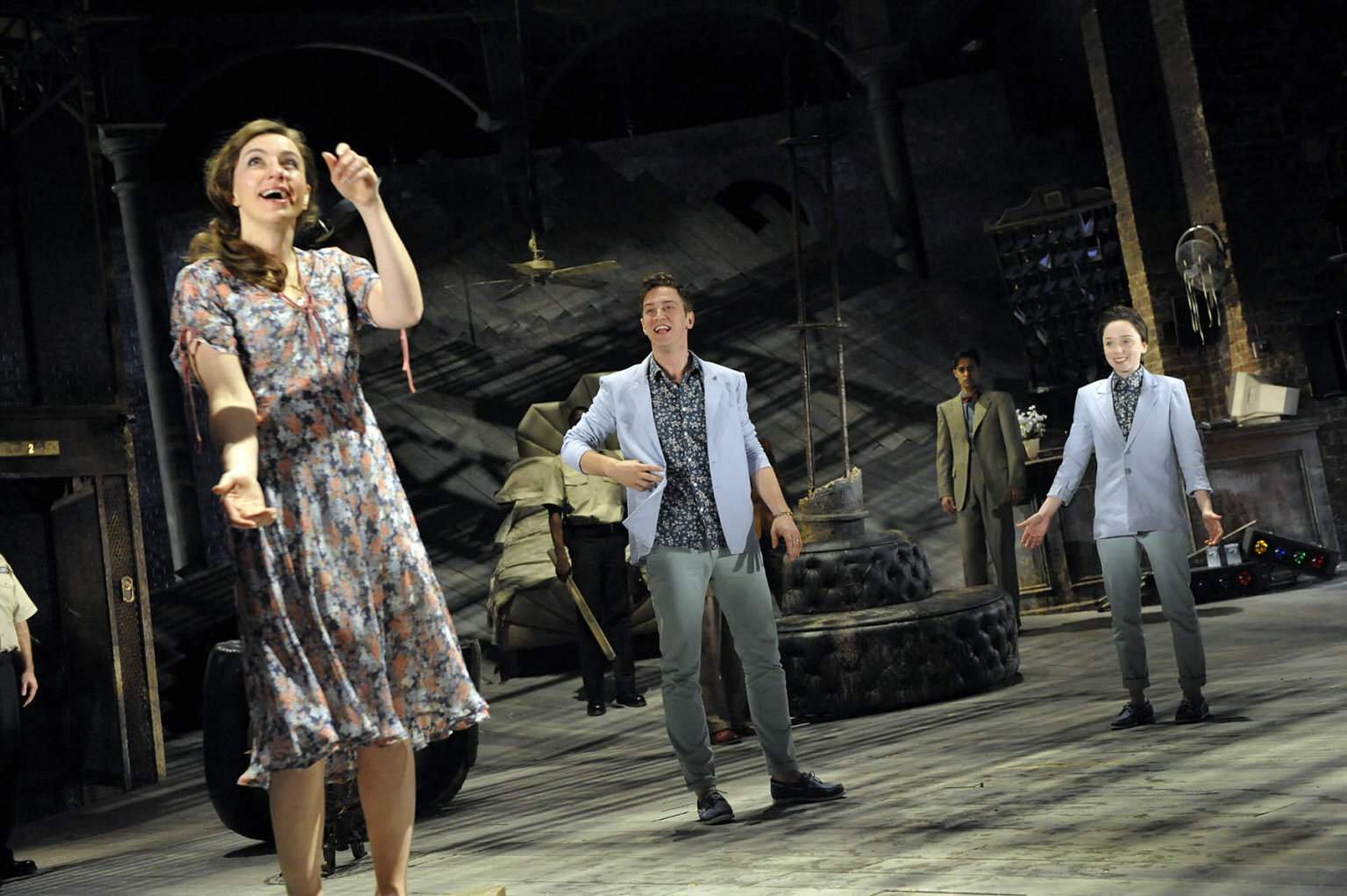Viola and Sebastian both stand behind a laughing Olivia, dressed in pale blue jackets and patterned shirts in the 2012 production of Twelfth Night.