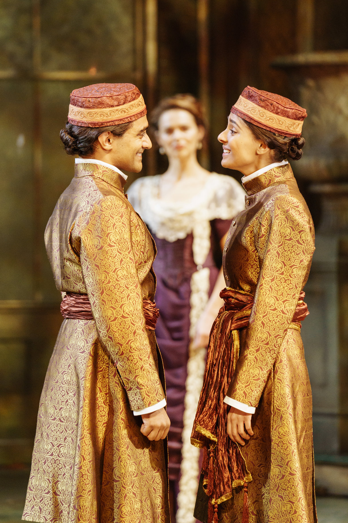 Viola and Sebastian stand face to face with Olivia in the background, both dressed in gold with identical hats, in the 2017 production of Twelfth Night.