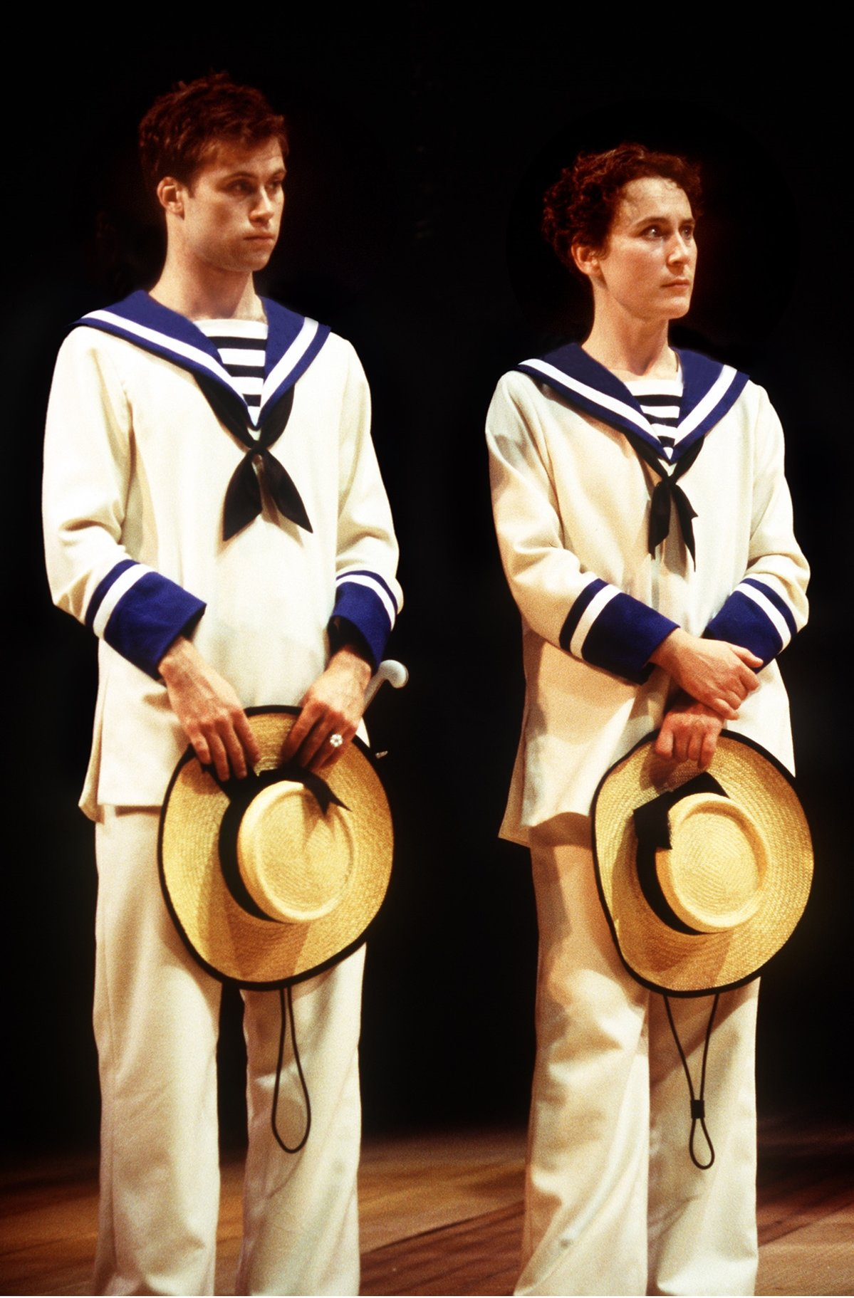 Viola and Sebastian stand side by side in sailor's uniforms with their arms crossed both holding large hats in the 1998 production of Twelfth Night.