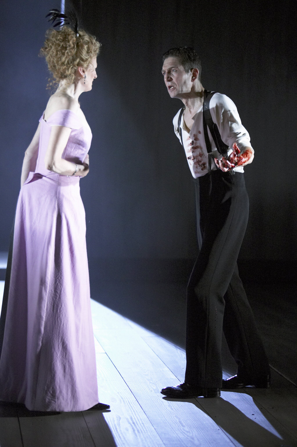A bloodied Macbeth talks with his wife.