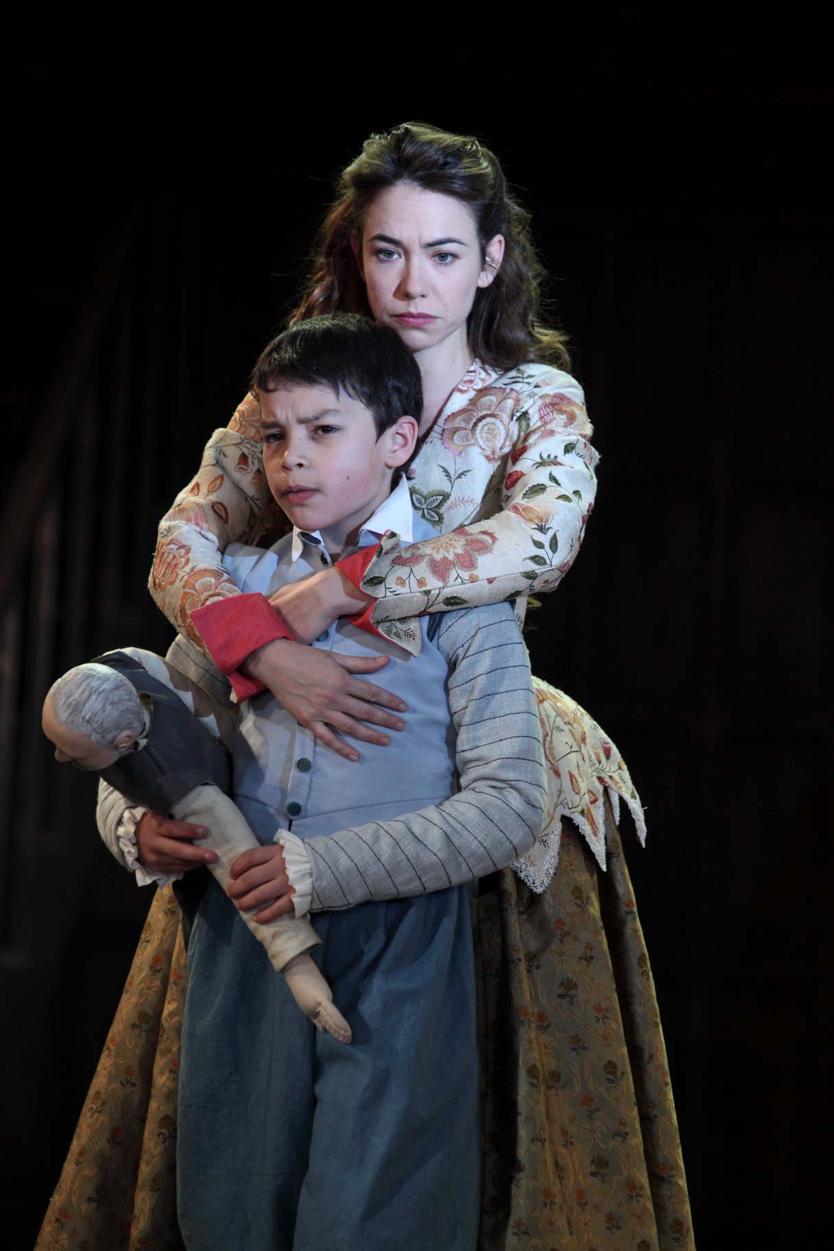 Lady Macduff holds onto her son.