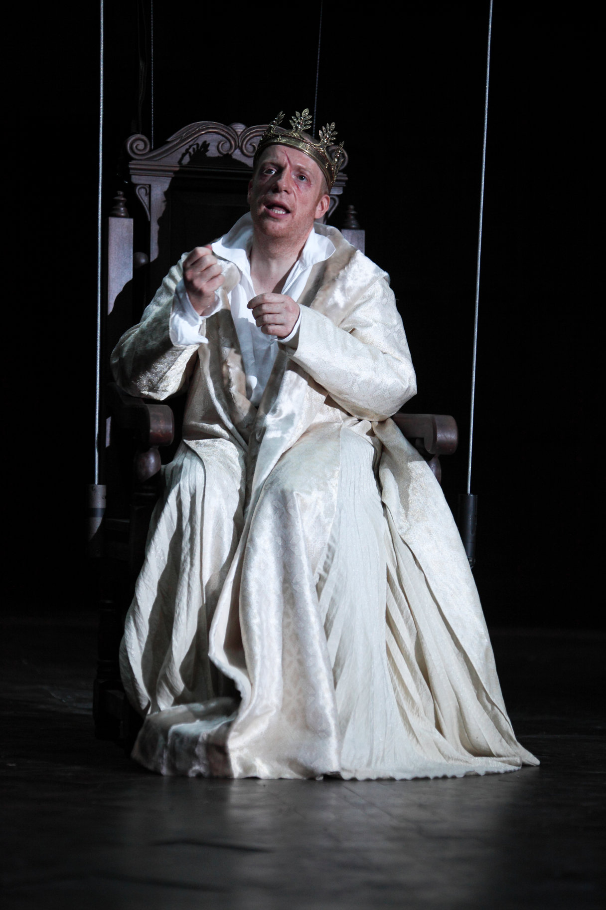Macbeth on his throne in white gown and golden crown