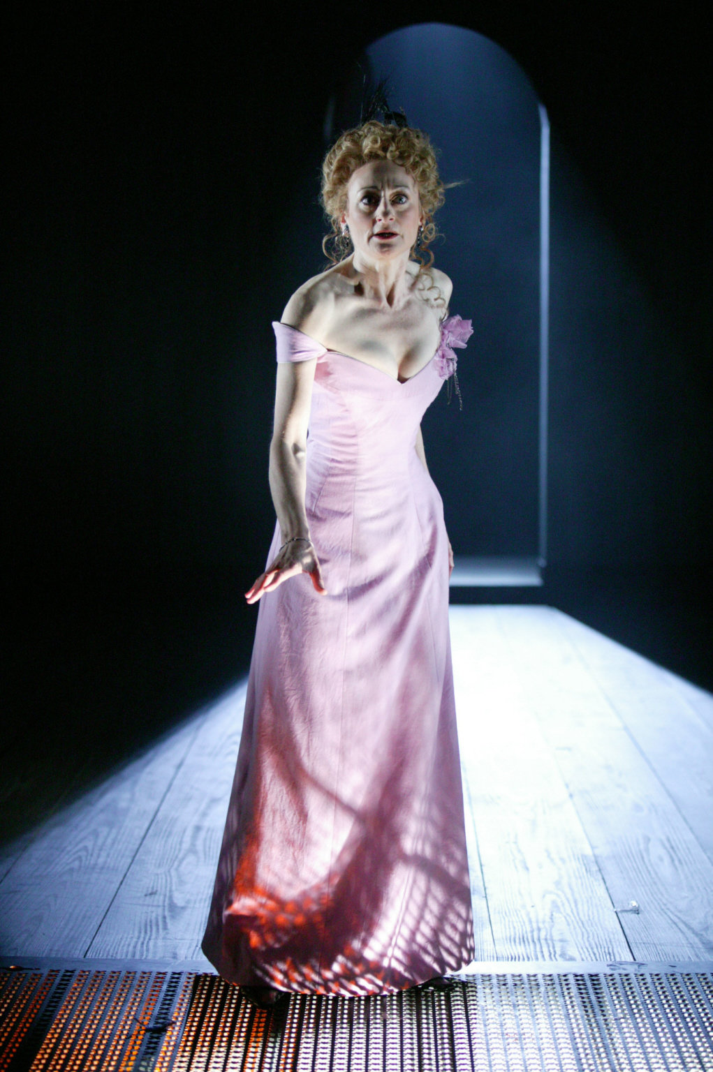 An apprehensive Lady Macbeth in a pink silk dress.
