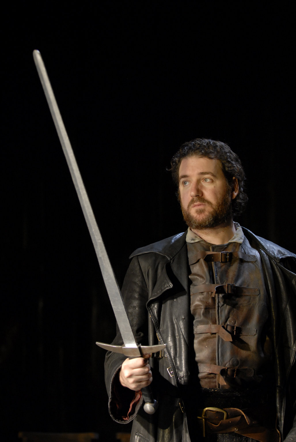 Macduff holds a sword in front of himself.