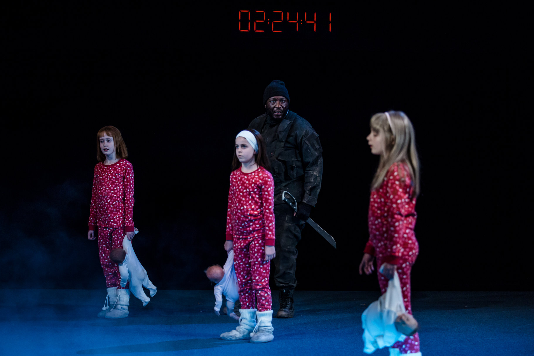 Banquo is frightened by the witches, who are three young girls in red pyjamas, carrying dolls.