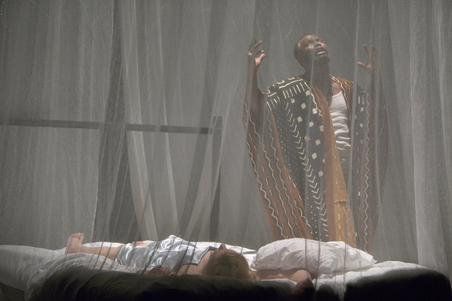 Othello stands over Desdemona's body.