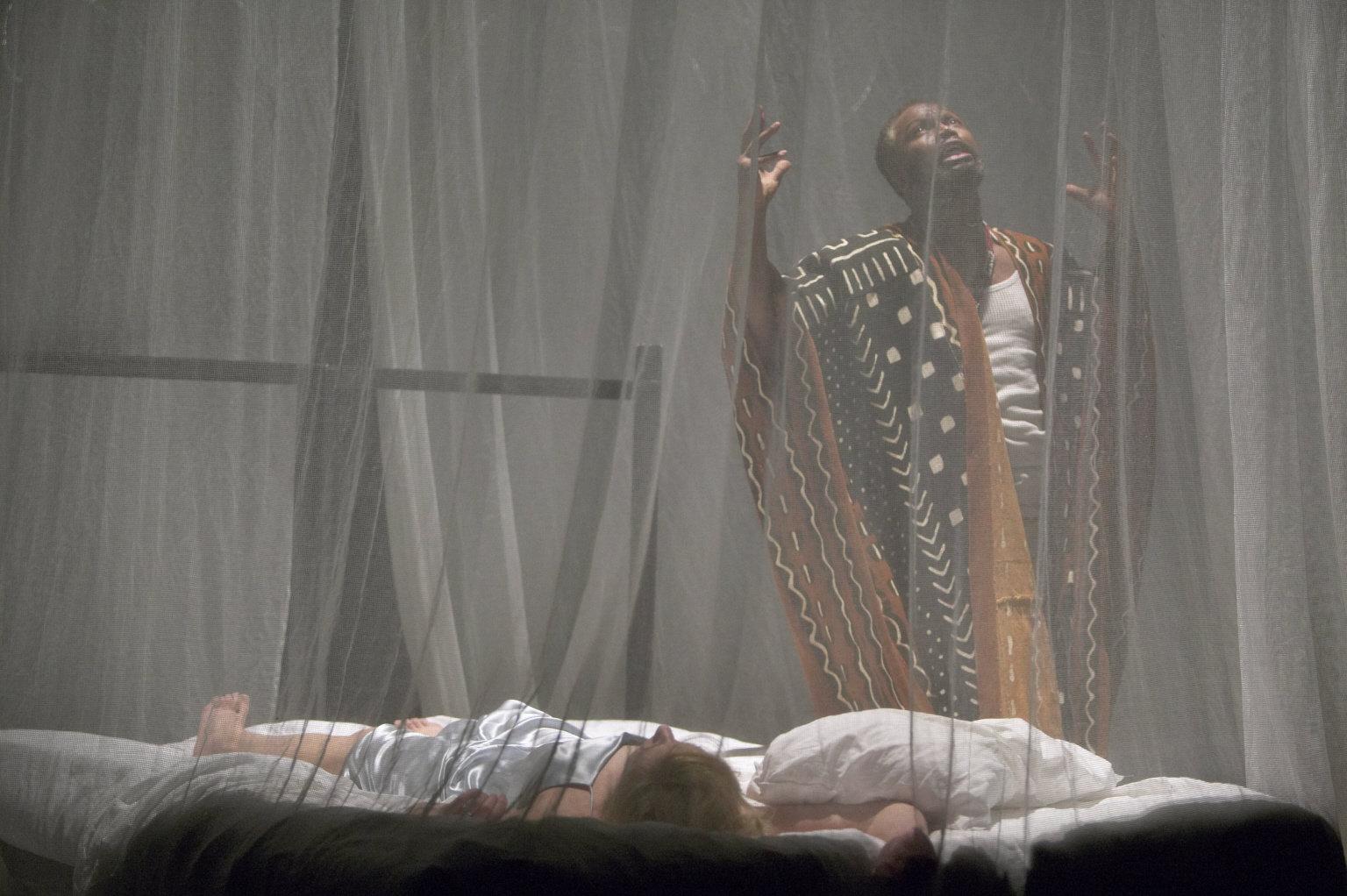 Othello stands over Desdemona's body.