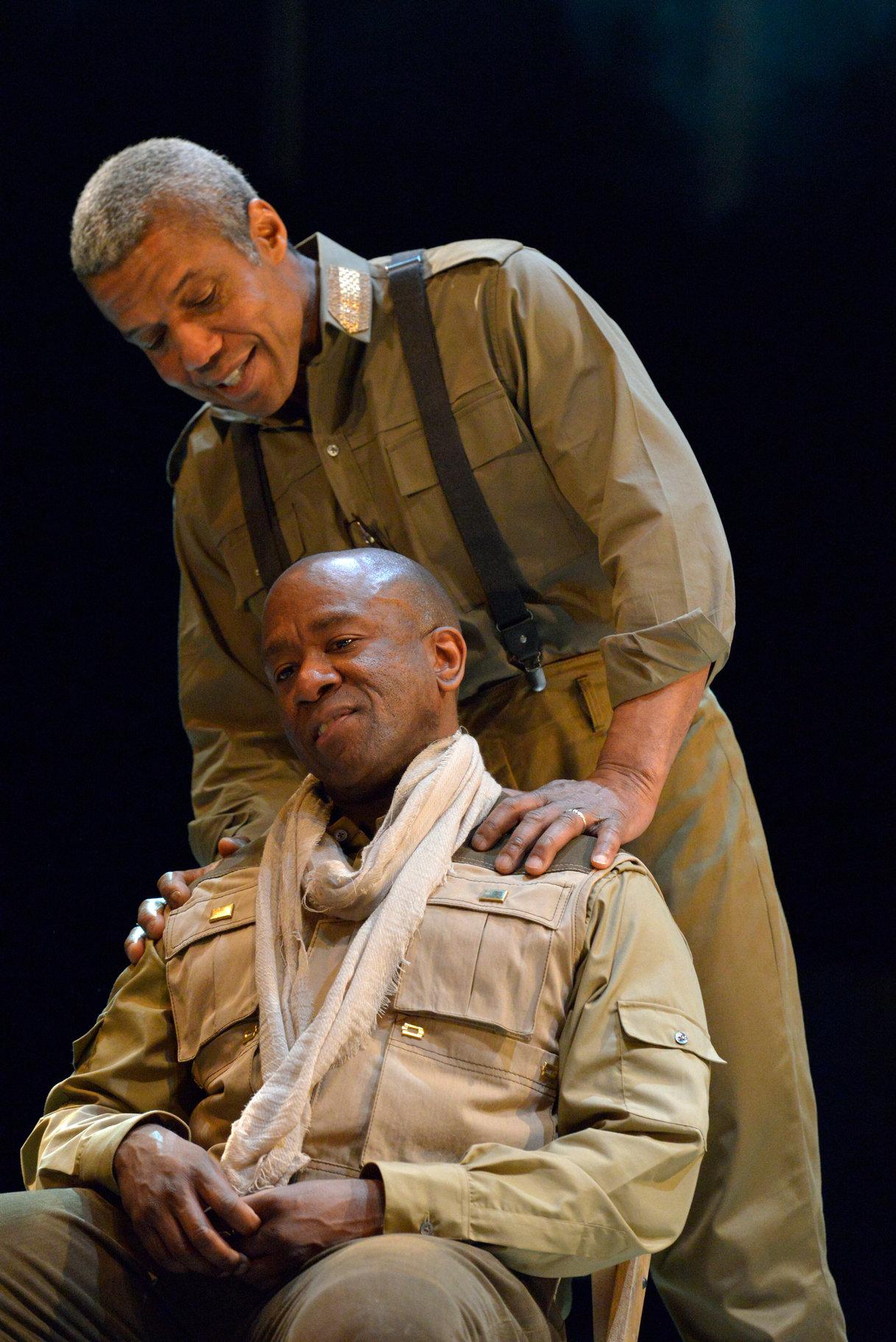 Othello stands behind Iago.