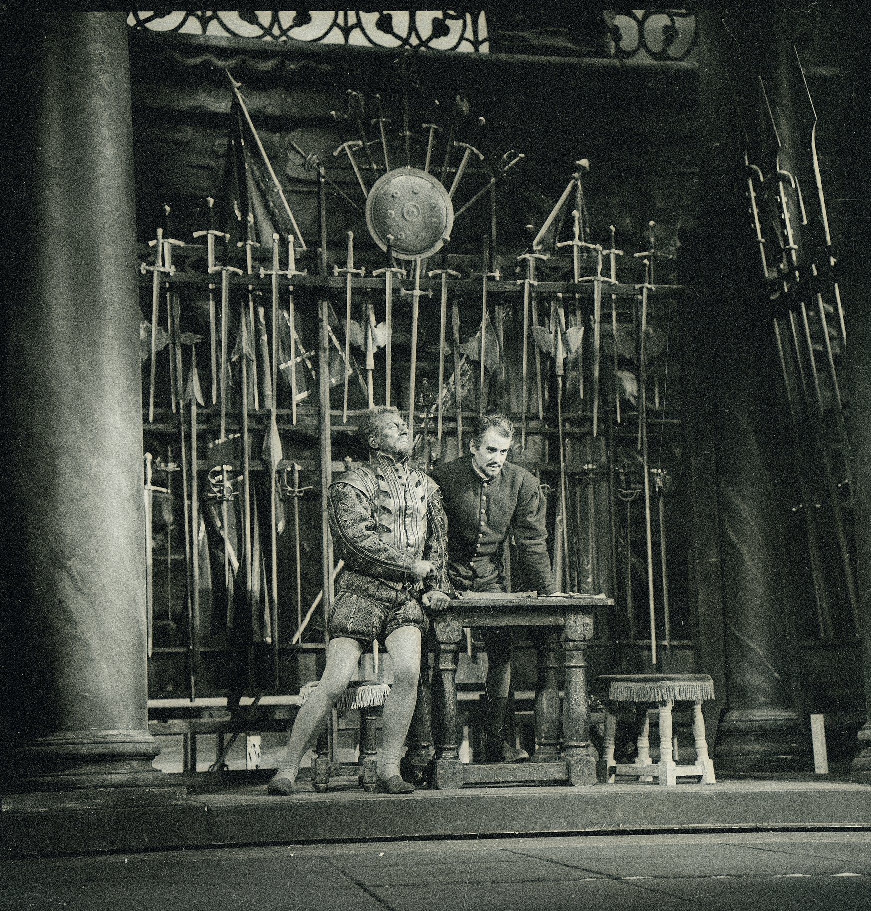 Othello and Iago in front of a rack of swords.