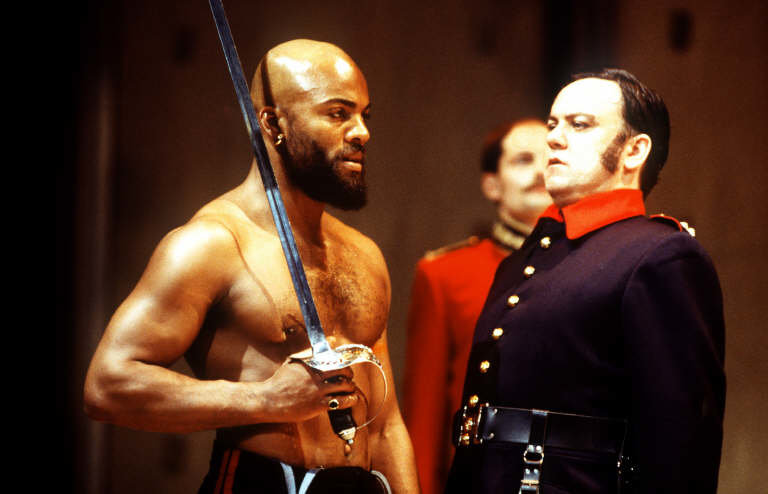 Iago looks concerned as Othello brandishes a sword.