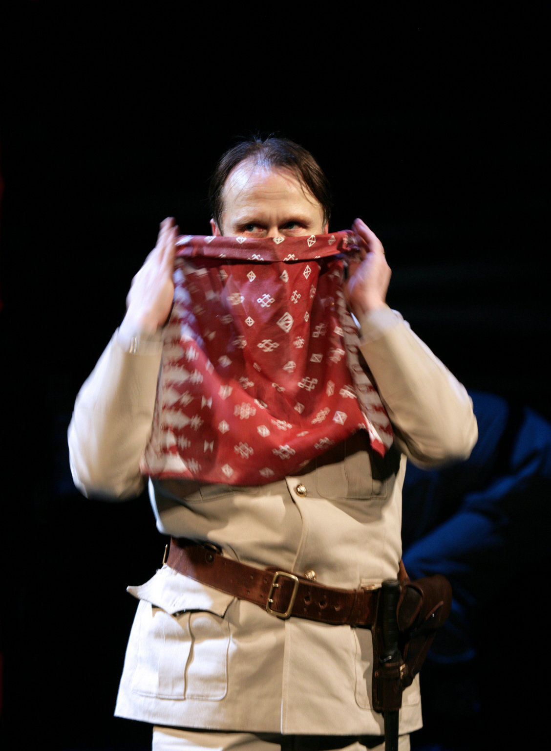 A man holds a handkerchief to his face.