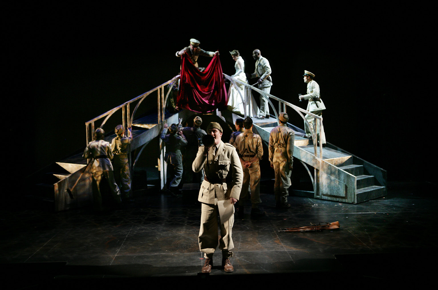 The cast of Othello on a stage bridge.