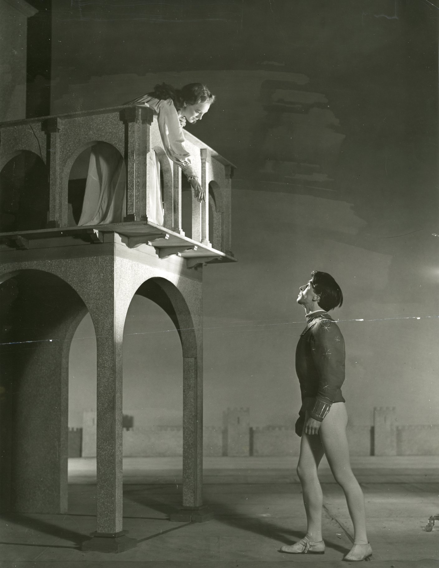 Juliet reaches down to Romeo from a balcony while he looks up at her.