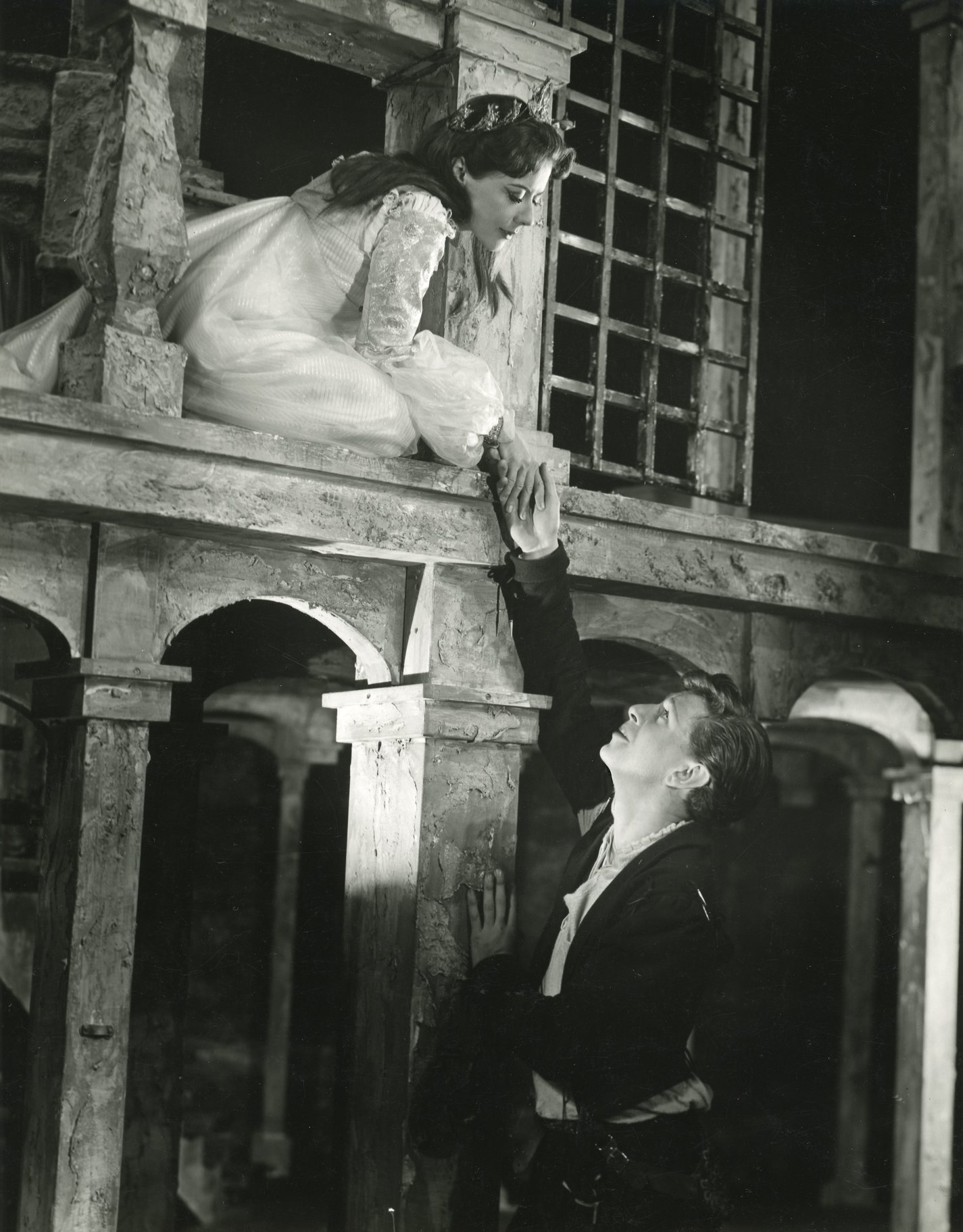 Romeo and Juliet hold hands from the balcony.