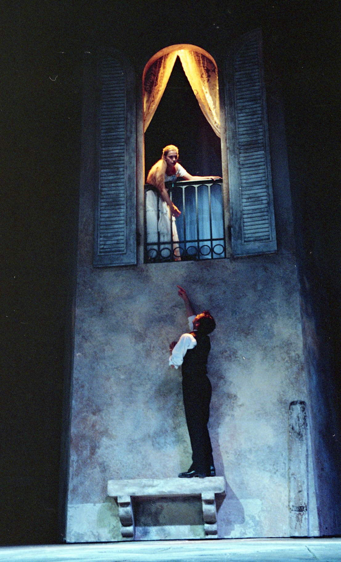 Romeo reaches up to Juliet, standing on a small bench to try and access her balcony and window.