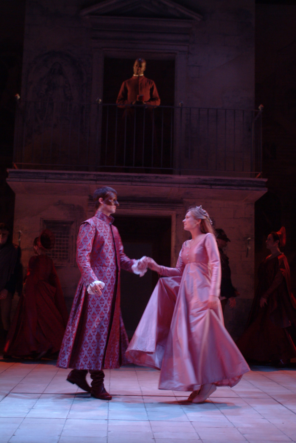Romeo and Juliet dance at the ball, with masks and formal clothes on.