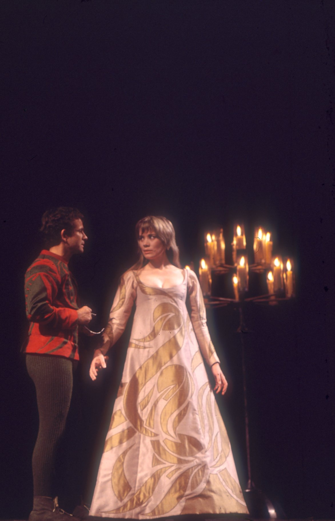 The lovers meet at the ball. Juliet is dressed in a white and gold dress and Romeo is dressed in red, there are candles behind them.