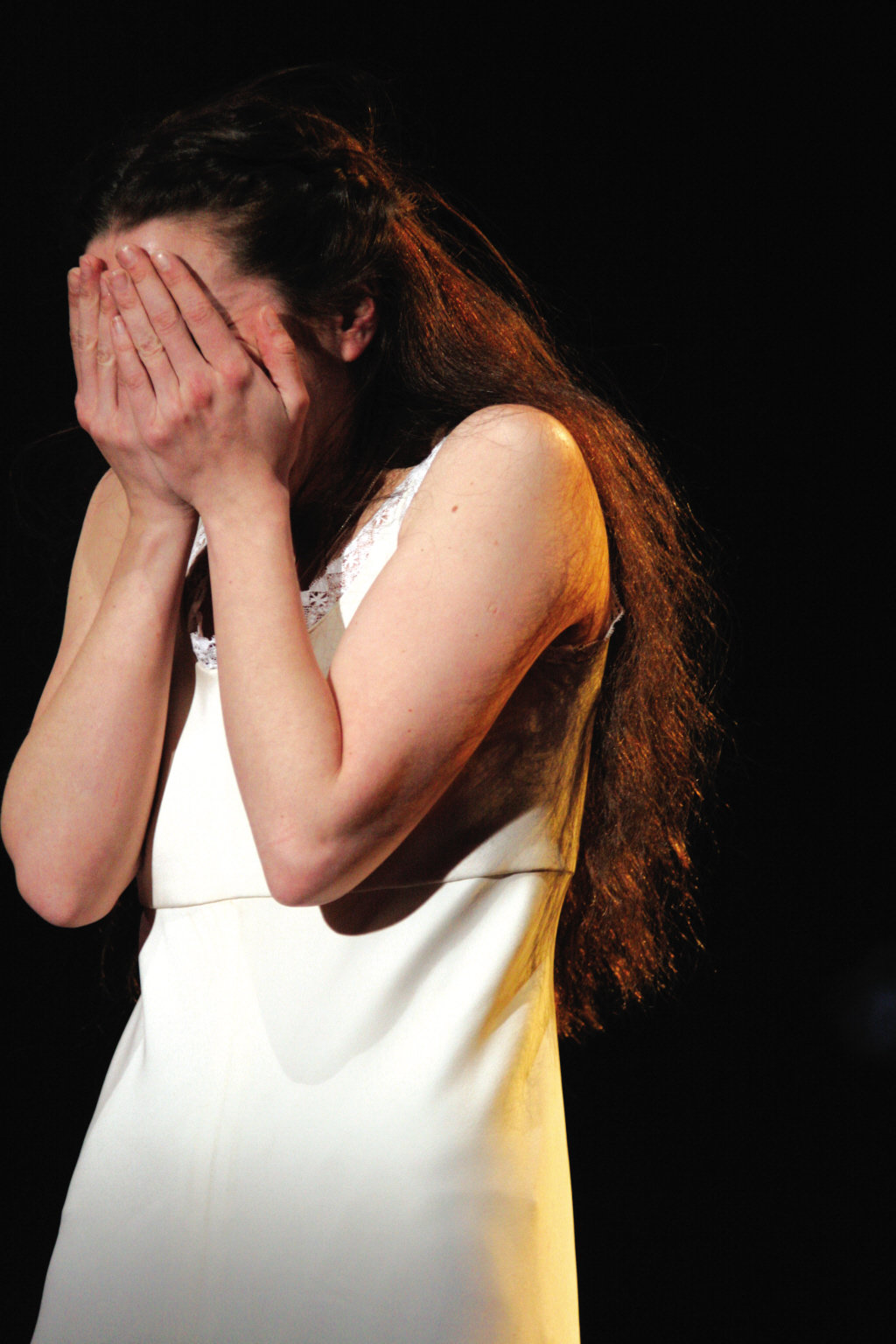 Juliet covers her face and cries, dressed in a simple white night dress.