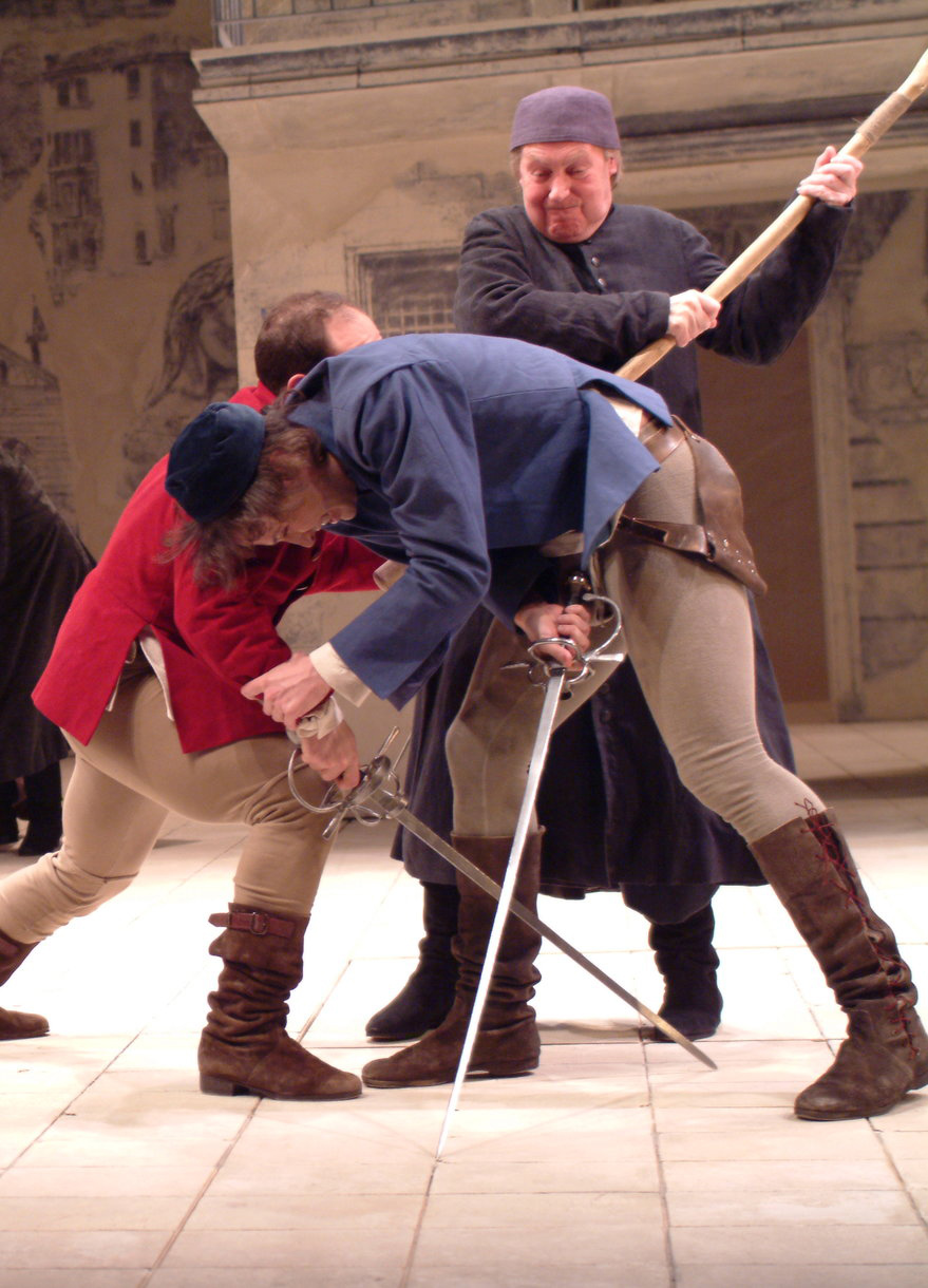 Two men fight with swords as another man tries to separate them with a stick.